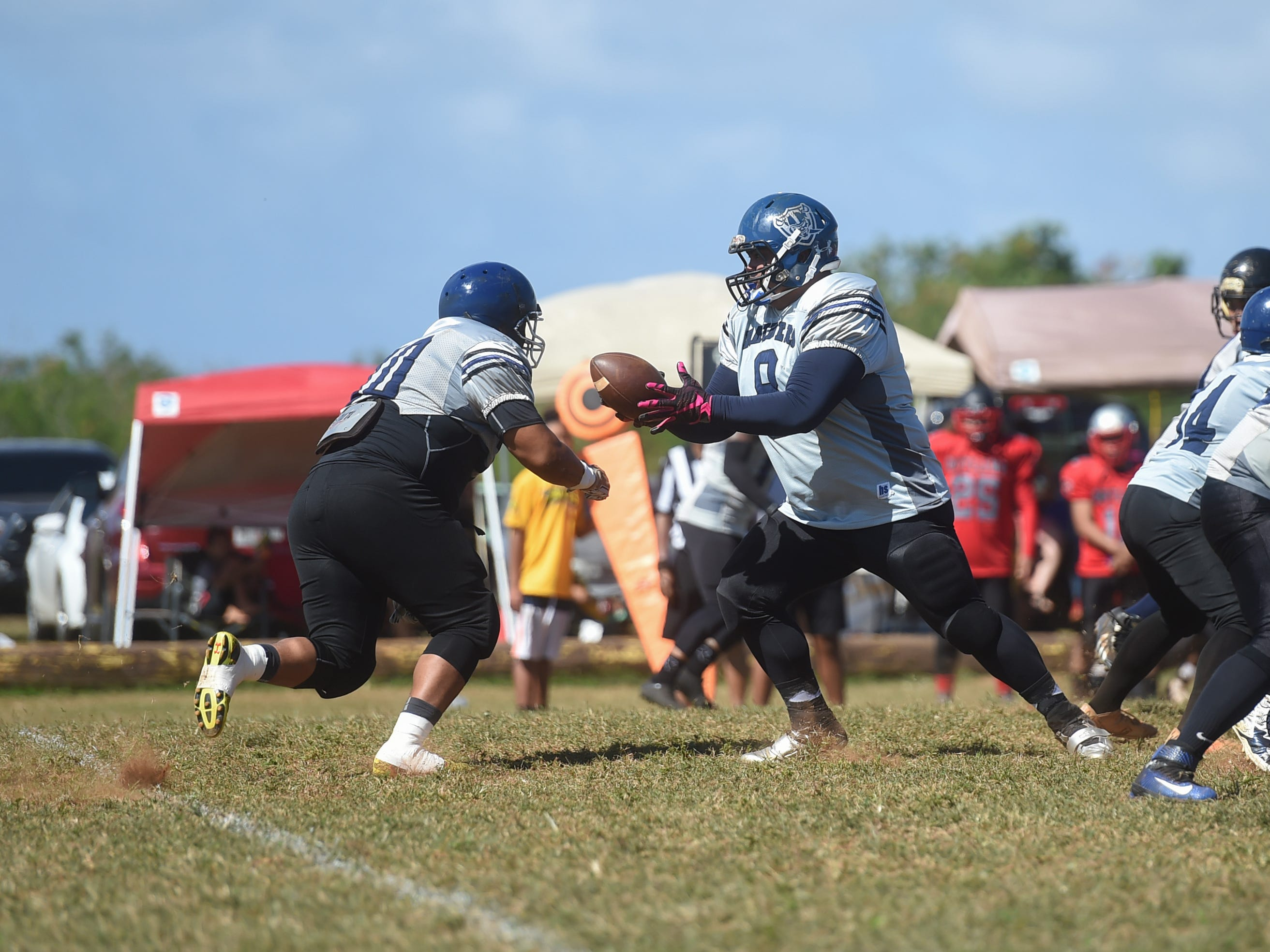 Guam Raiders player Danny Manibusan (8) attempts to make a handoff against the Outlaws during their Budweiser Guahan Varsity Football League game at Eagles Field in Mangilao, Feb. 16, 2019.