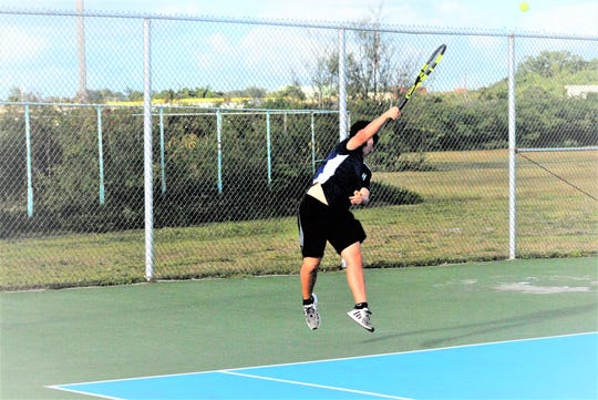 Harvest Christian Academy's Abraham Kim serves against FD during a doubles 2 match on Friday at the University of Guam tennis courts.