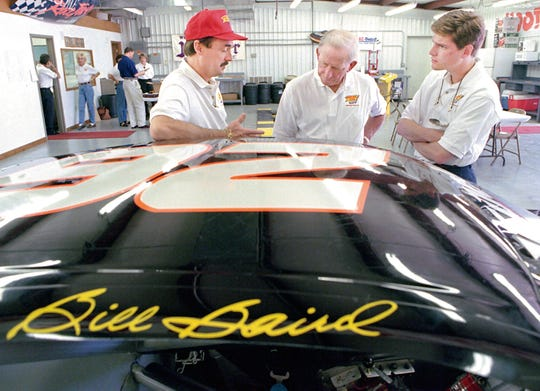 In his Sturgis race shop, Bill Baird, left, talks about one of his cars with sponsors Ray and Kent Preston. Before the 1997 racing season.