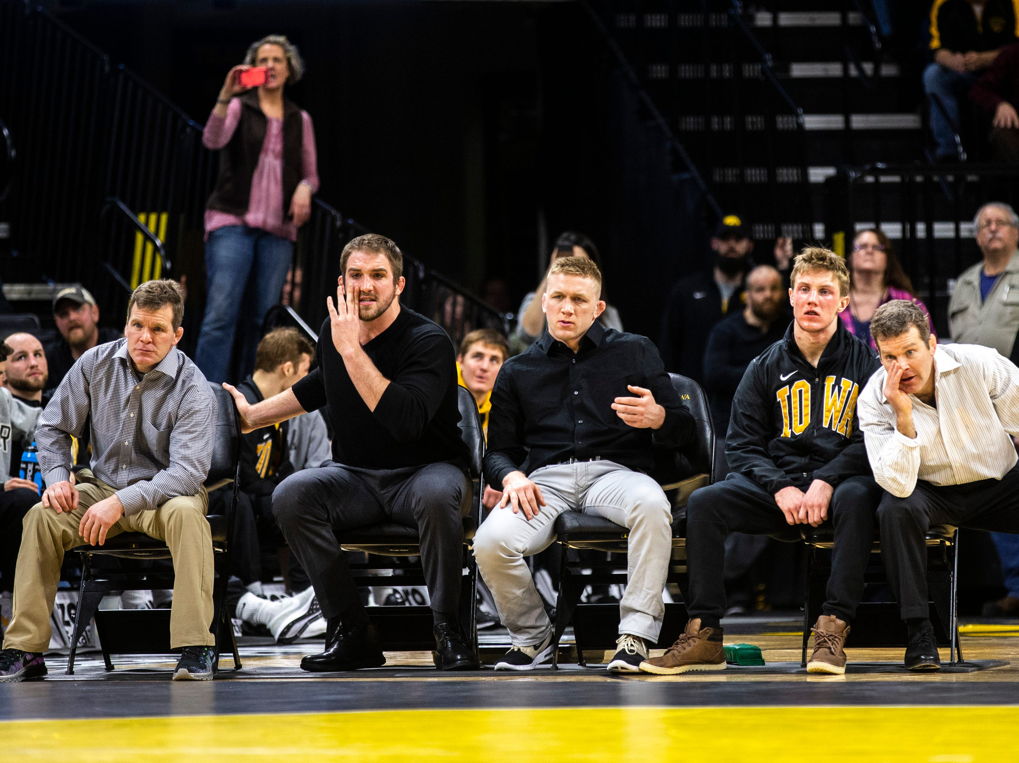 Iowa associate head coach Terry Brands, assistants Bobby Telford and Ryan Morningstar, 141-pounder Max Murin and head coach Tom Brands watch a match from the bench during a NCAA Big Ten Conference wrestling dual on Friday, Feb. 15, 2019 at Carver-Hawkeye Arena in Iowa City, Iowa.
