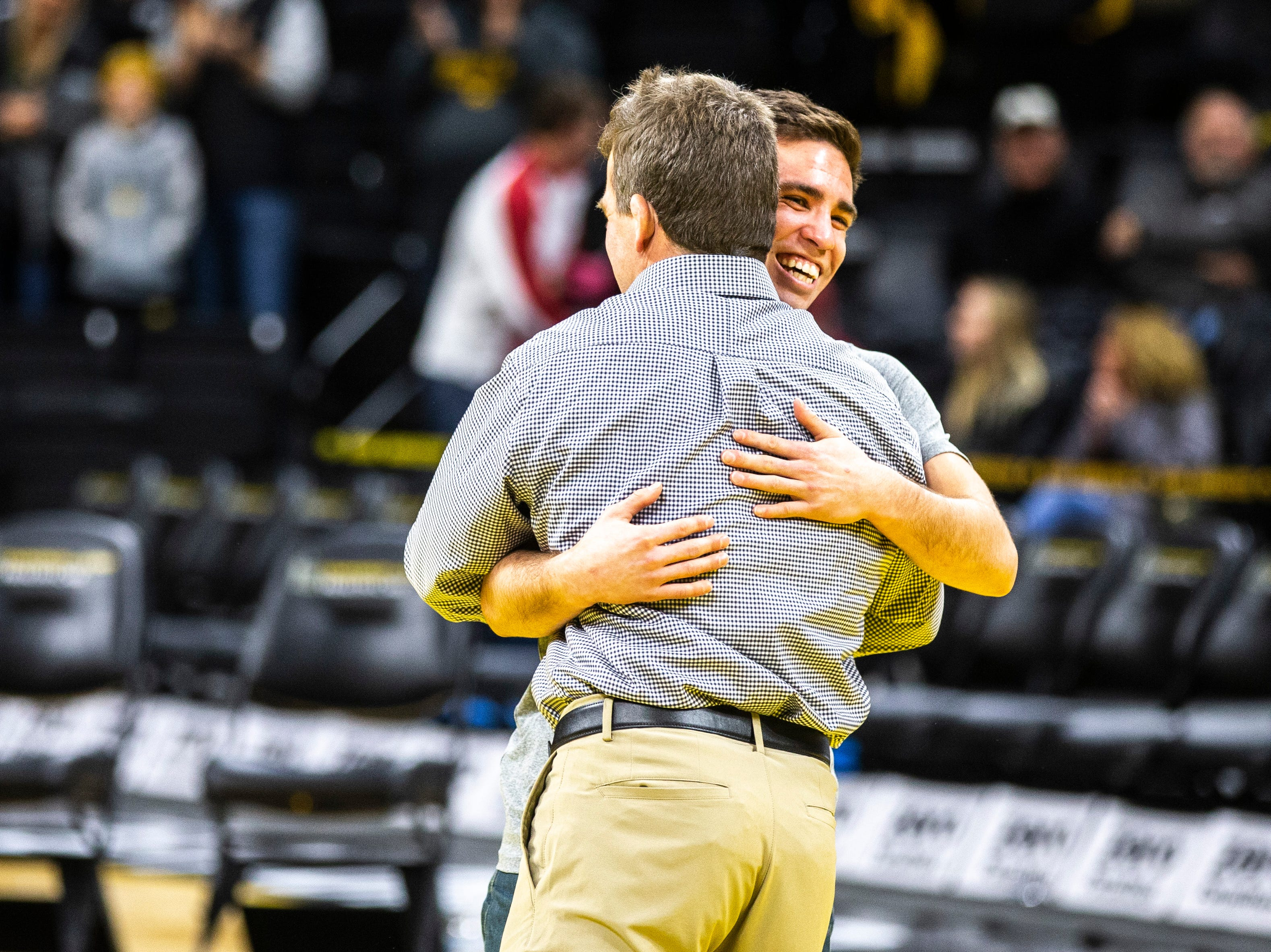 Iowa associate head coach Terry Brands hugs senior 125-pounder Perez Perez after a NCAA Big Ten Conference wrestling dual on Friday, Feb. 15, 2019 at Carver-Hawkeye Arena in Iowa City, Iowa.