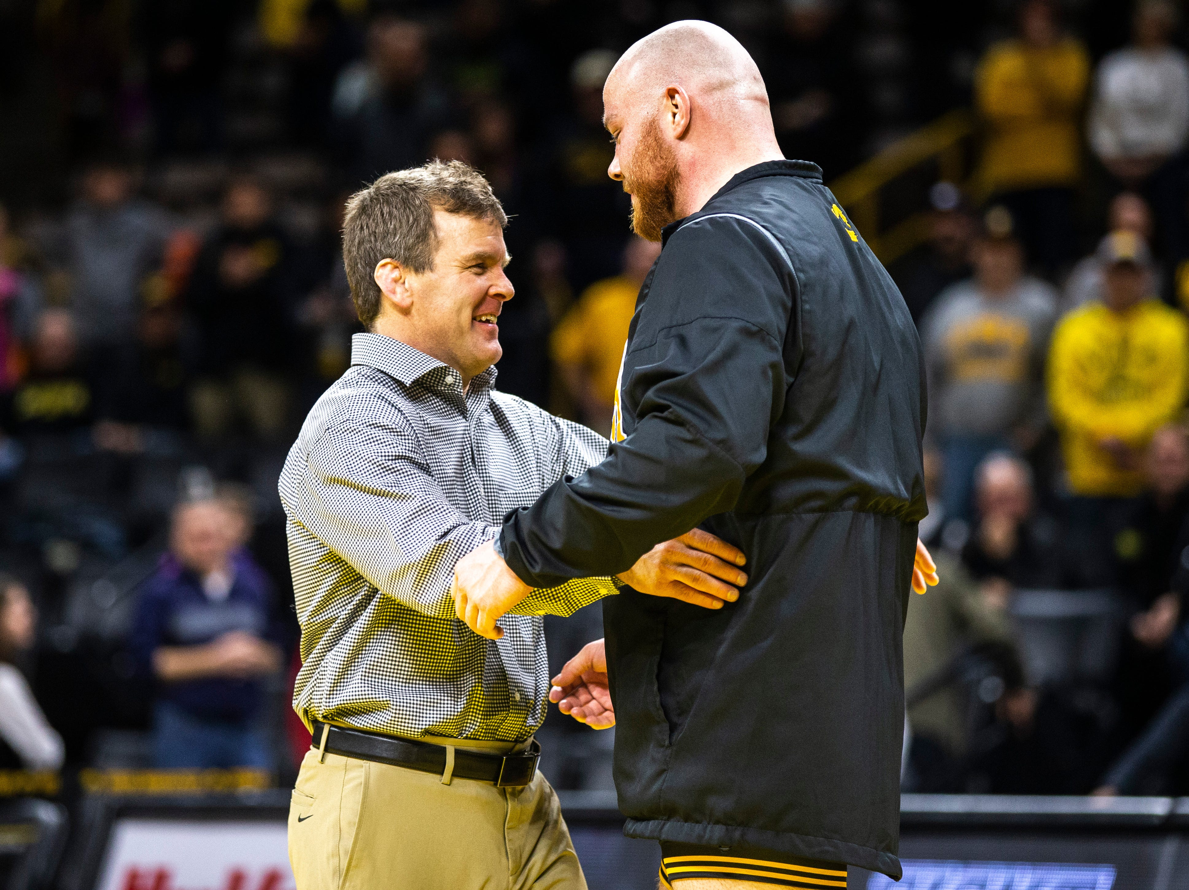 Iowa associate head coach Terry Brands embraces senior 285-pounder Sam Stoll during a NCAA Big Ten Conference wrestling dual on Friday, Feb. 15, 2019 at Carver-Hawkeye Arena in Iowa City, Iowa.