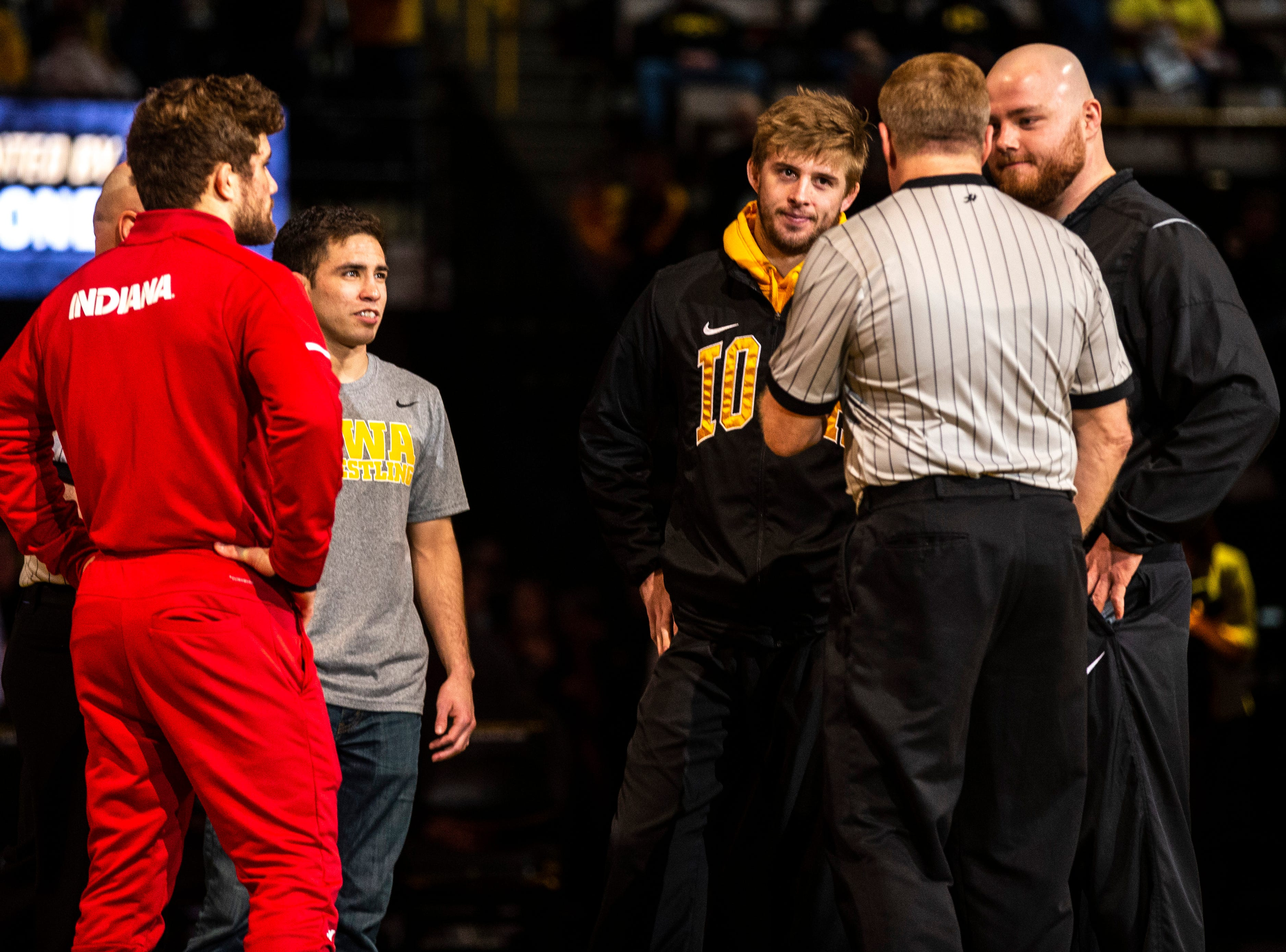 Iowa seniors Perez Perez, Mitch Bowman and Sam Stoll head to the mat as captains during a NCAA Big Ten Conference wrestling dual against Indiana on Friday, Feb. 15, 2019 at Carver-Hawkeye Arena in Iowa City, Iowa.