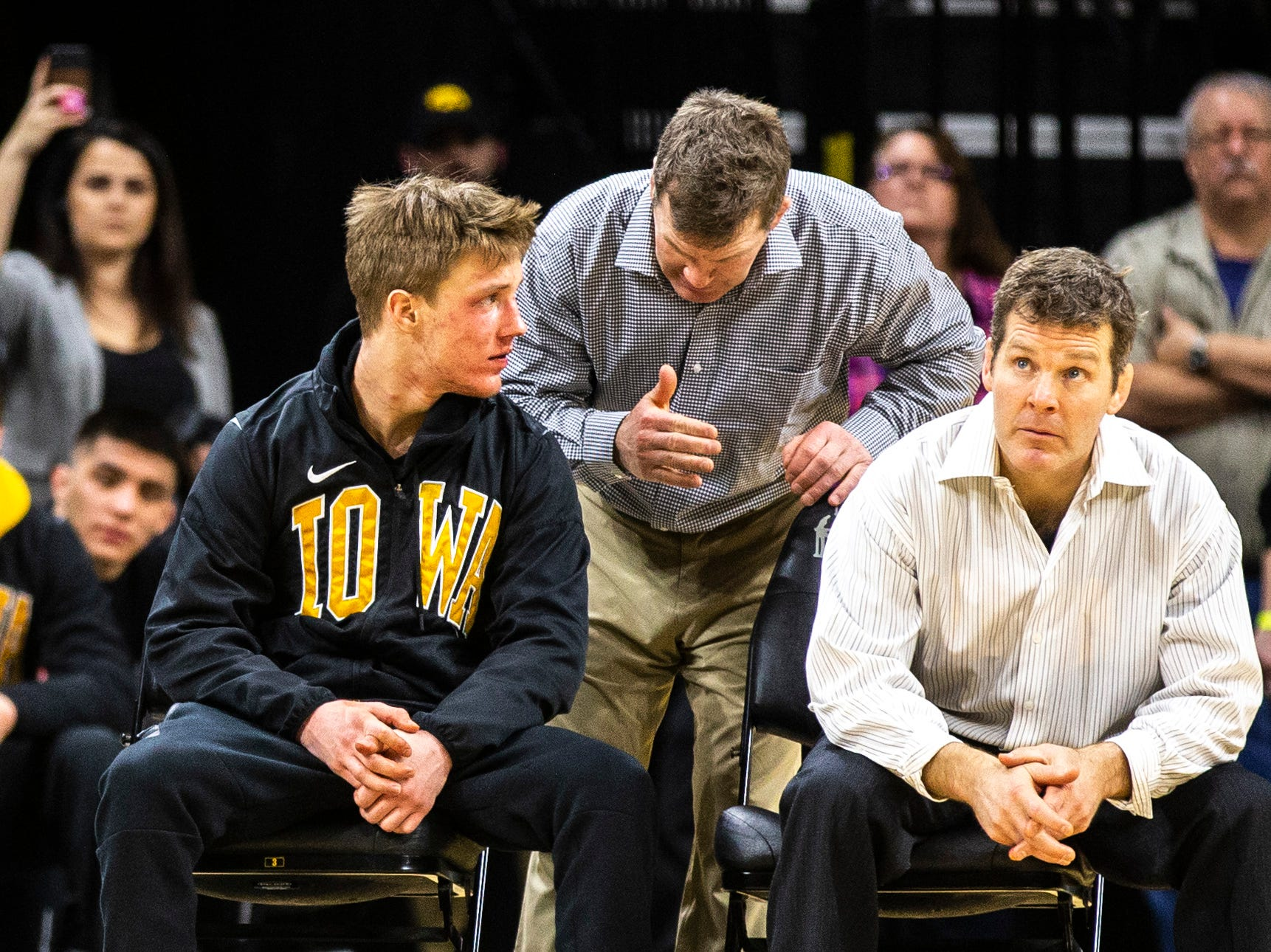 Iowa associate head coach Terry Brands, center, talks with 141-pounder Max Murin, left, while head coach Tom Brands watches a match during a NCAA Big Ten Conference wrestling dual on Friday, Feb. 15, 2019 at Carver-Hawkeye Arena in Iowa City, Iowa.