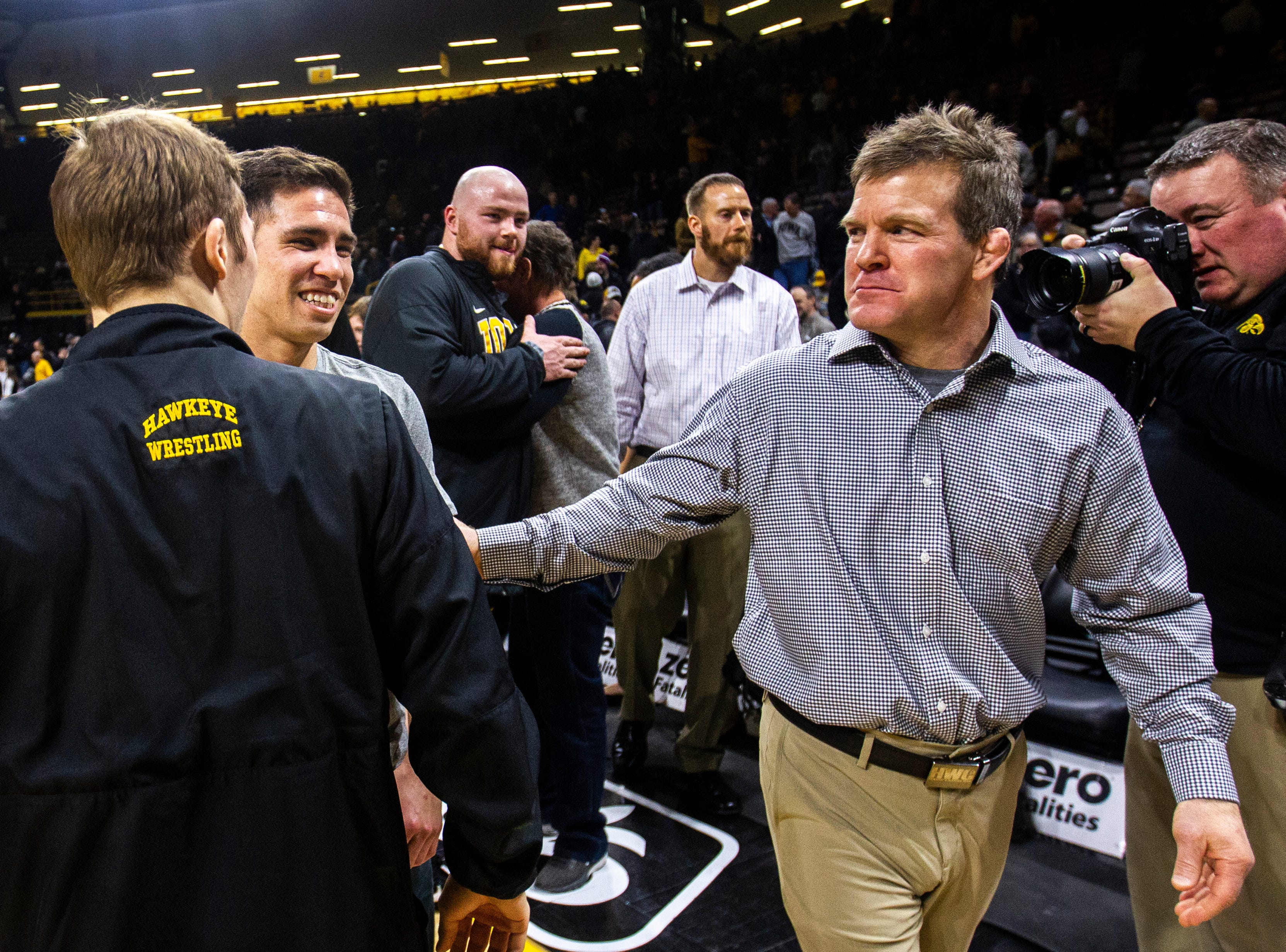Iowa associate head coach Terry Brands joins Iowa 125-pounders Perez Perez, second from left, and Spencer Lee after a NCAA Big Ten Conference wrestling dual on Friday, Feb. 15, 2019 at Carver-Hawkeye Arena in Iowa City, Iowa.