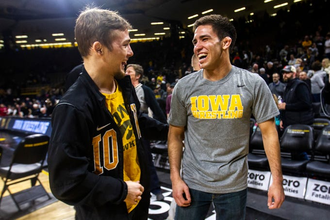 Iowa's Spencer Lee, left, and senior Perez Perez talk after a NCAA Big Ten Conference wrestling dual on Friday, Feb. 15, 2019 at Carver-Hawkeye Arena in Iowa City, Iowa.