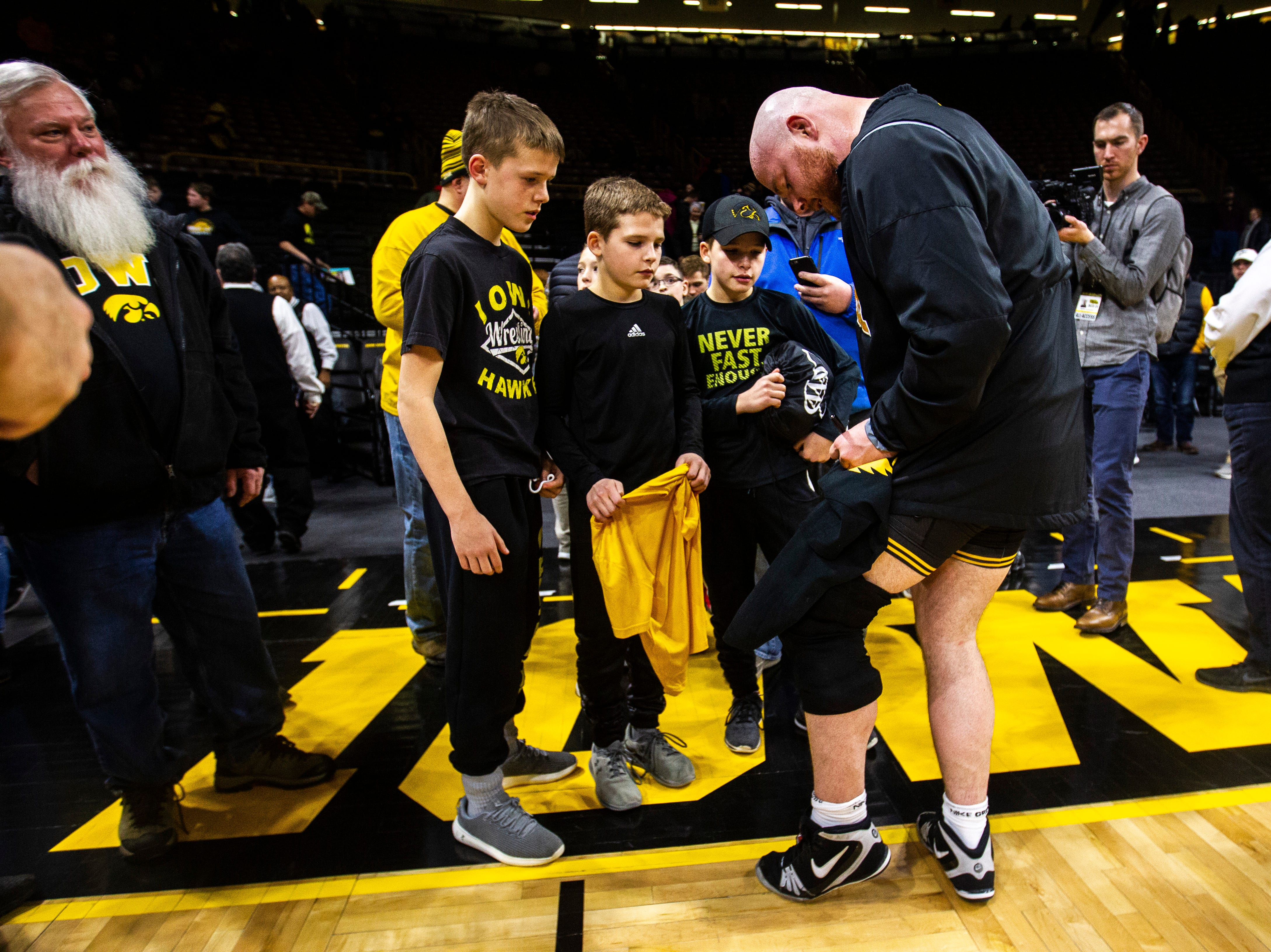 Iowa senior 285-pounder Sam Stoll signs autographs for fans after a NCAA Big Ten Conference wrestling dual on Friday, Feb. 15, 2019 at Carver-Hawkeye Arena in Iowa City, Iowa.