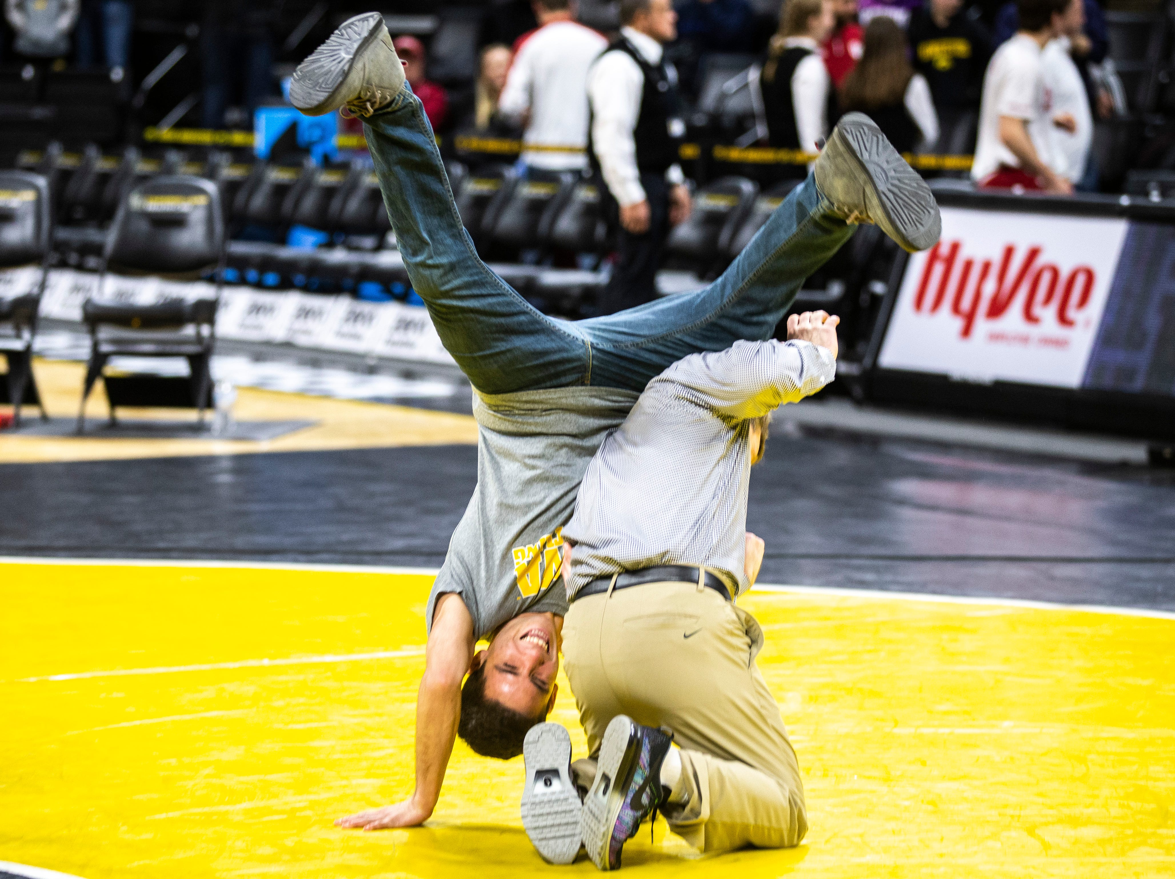 Iowa associate head coach Terry Brands gets a takedown on senior 125-pounder Perez Perez during a NCAA Big Ten Conference wrestling dual on Friday, Feb. 15, 2019 at Carver-Hawkeye Arena in Iowa City, Iowa.