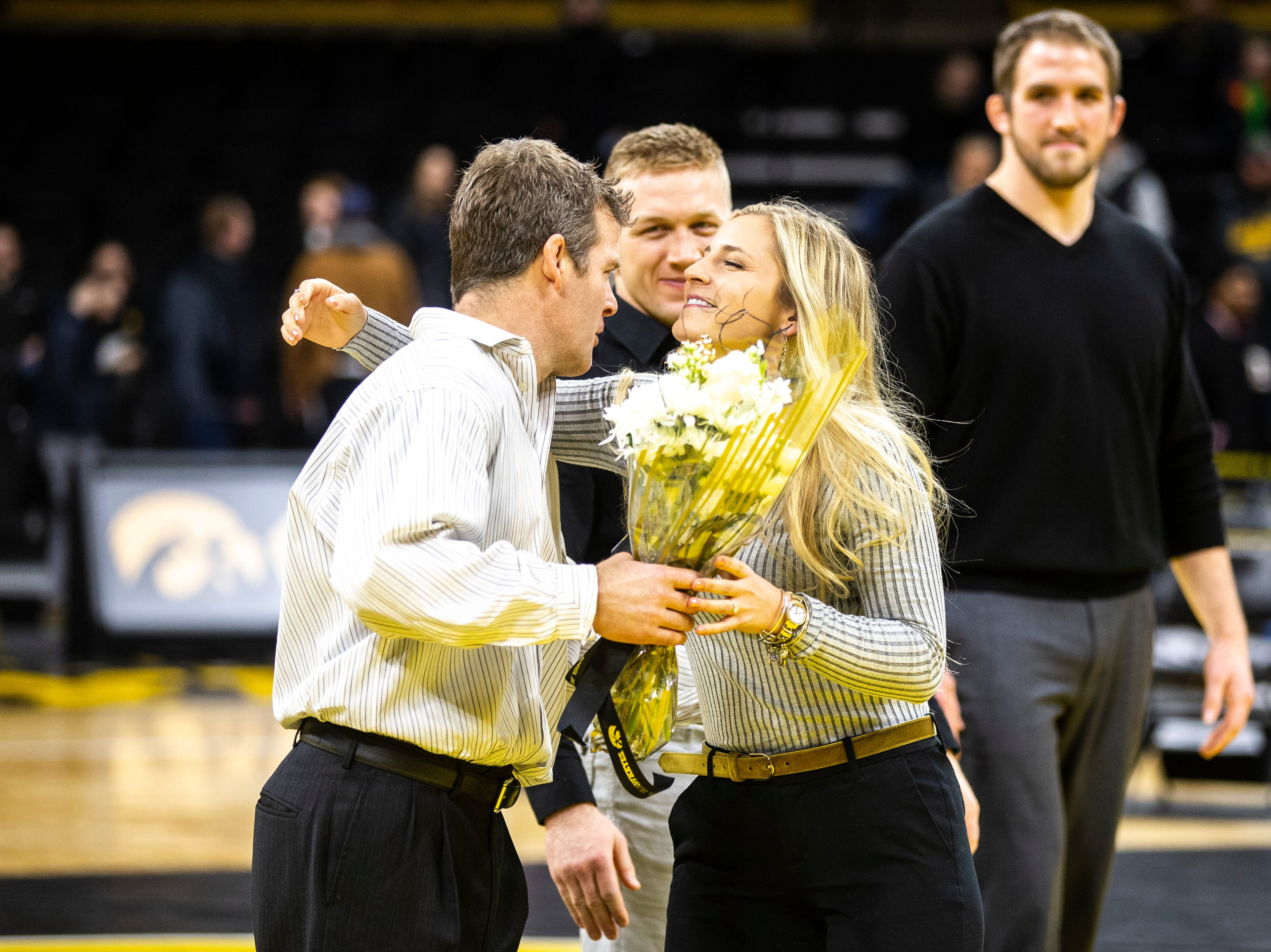 Iowa head coach Tom Brands, left, gives Iowa senior manager Moriah Stickley a hug during a NCAA Big Ten Conference wrestling dual on Friday, Feb. 15, 2019 at Carver-Hawkeye Arena in Iowa City, Iowa.
