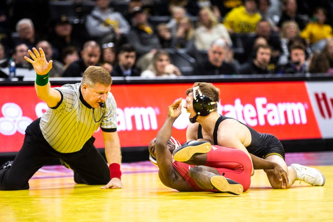 Iowa's Spencer Lee, top, reacts after taking a hand to the face while wrestling Indiana's Elijah Oliver at 125 during a NCAA Big Ten Conference wrestling dual on Friday, Feb. 15, 2019 at Carver-Hawkeye Arena in Iowa City, Iowa.