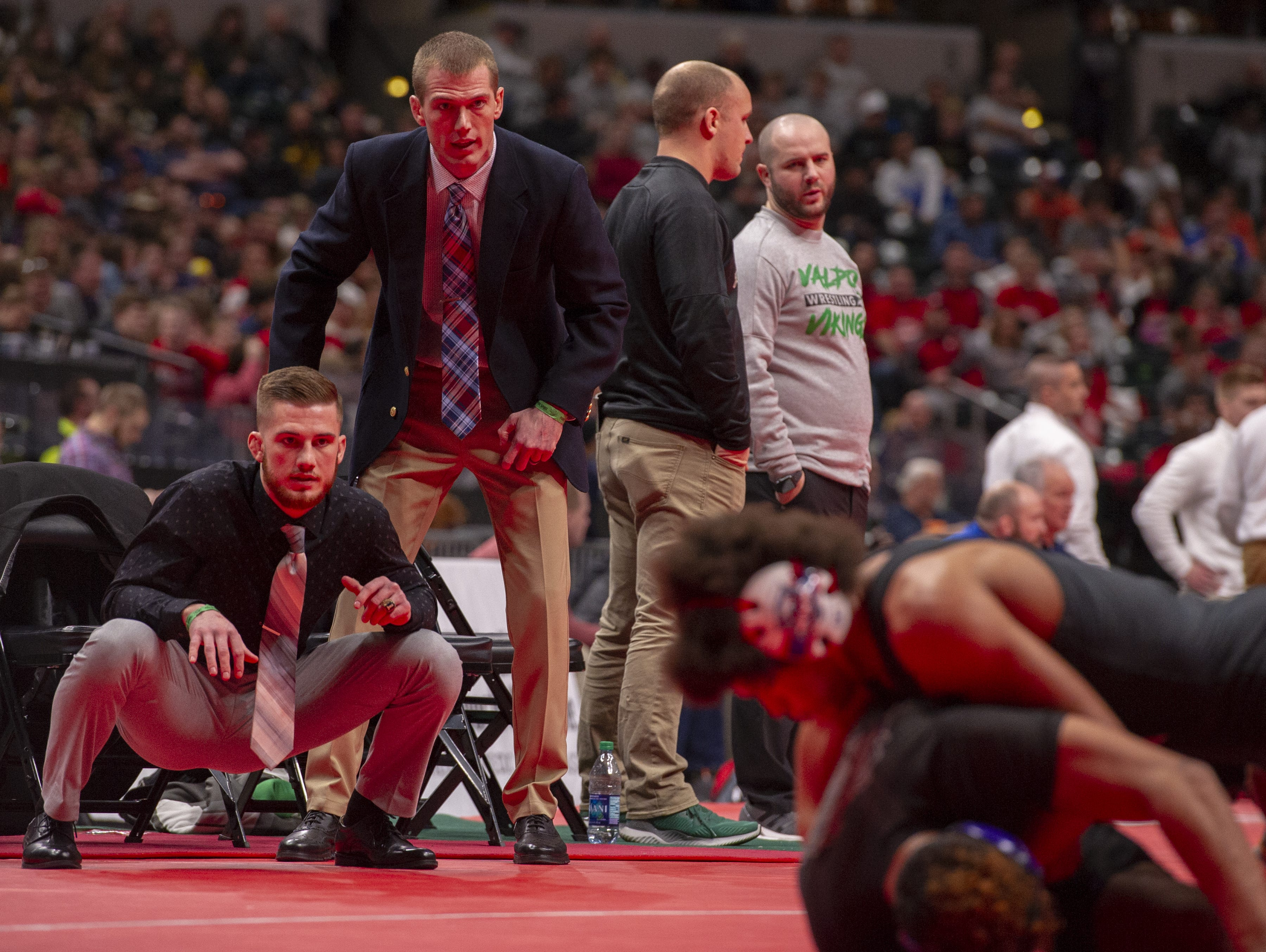 Roncalli High School head coach Wade McClurg, right and assistant coach Riley McClurg, brothers, watch as Elija Mahan competes in the 170-pound weight class during the first day of competition in the 81st Annual IHSAA Wrestling State Finals at Bankers Life Fieldhouse in Indianapolis, Friday, Feb. 15, 2019.
