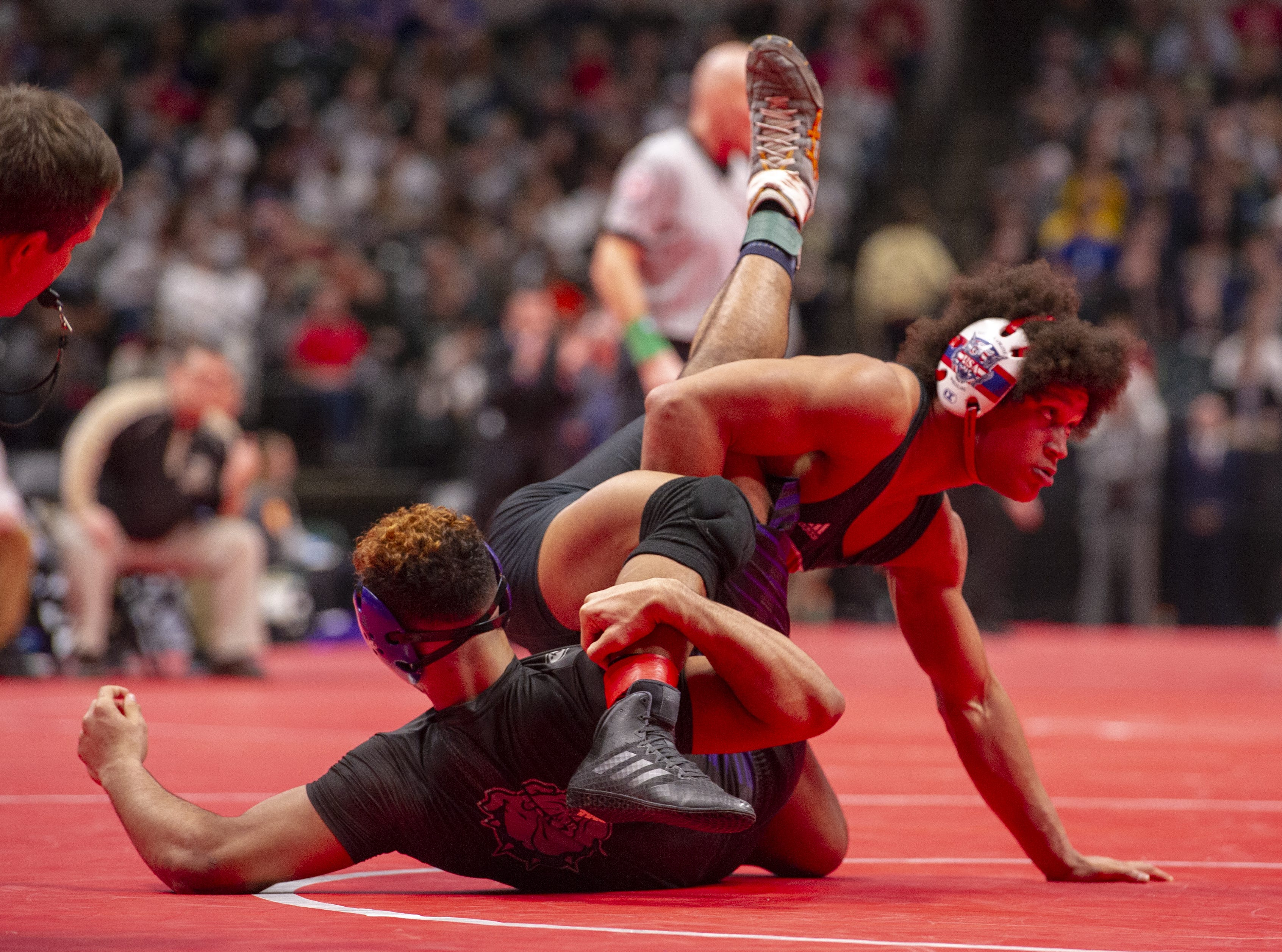 Roncalli High School wrestler Elijah Mahan, top, wrestles Brownsburg High School wrestler Thierry Jean-Baptiste in the 170-pound weight class during the first day of competition in the 81st Annual IHSAA Wrestling State Finals at Bankers Life Fieldhouse in Indianapolis, Friday, Feb. 15, 2019.