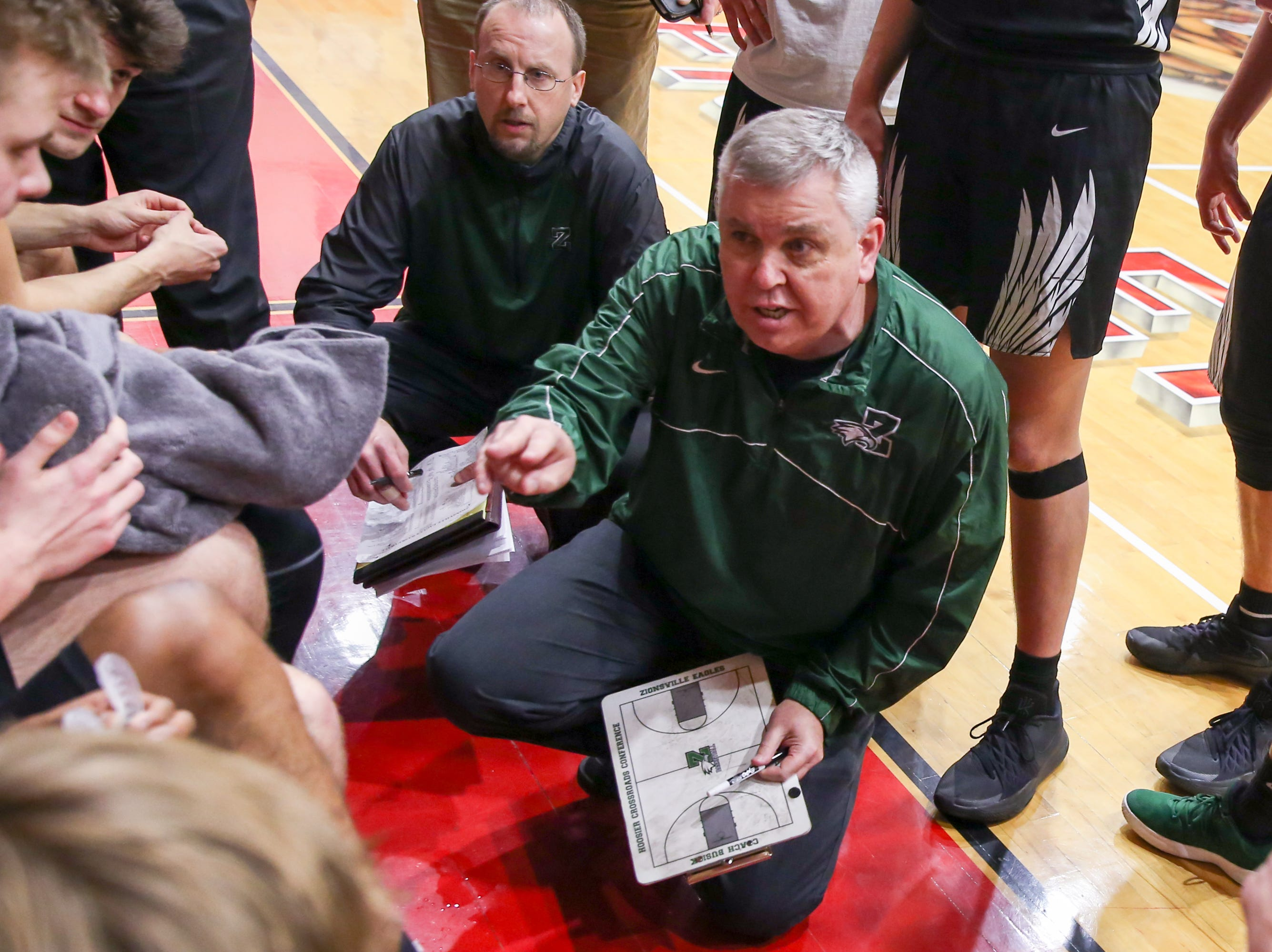 Zionsville High Coach Shaun Busick laid out plans for the 4th quarter play during the second half of Zionsville vs. Fishers high school boys varsity basketball game held at Fishers High School, February 15, 2019.