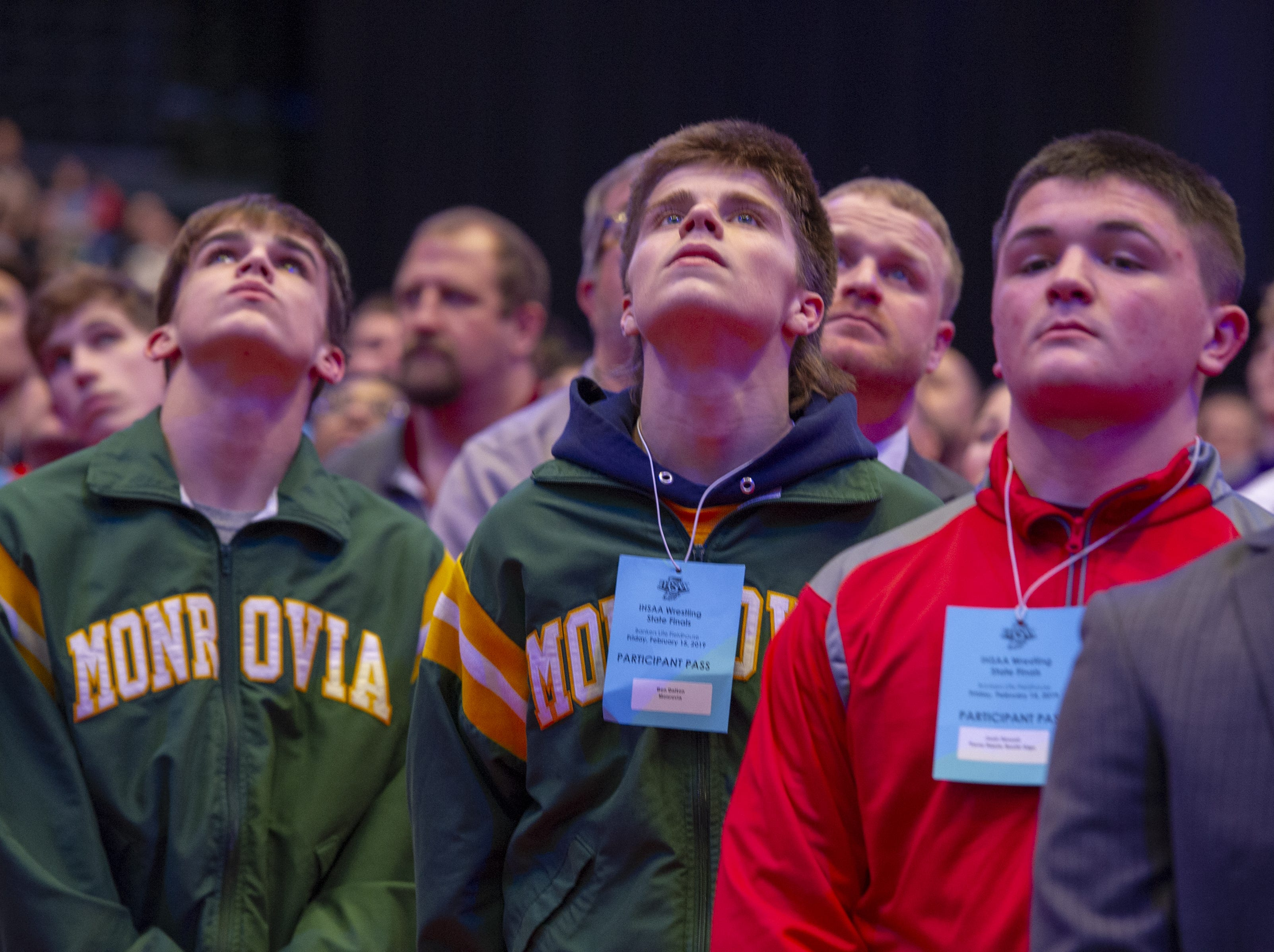 Wrestlers listen to the National Anthem before the first day of competition in the 81st Annual IHSAA Wrestling State Finals at Bankers Life Fieldhouse in Indianapolis, Friday, Feb. 15, 2019.