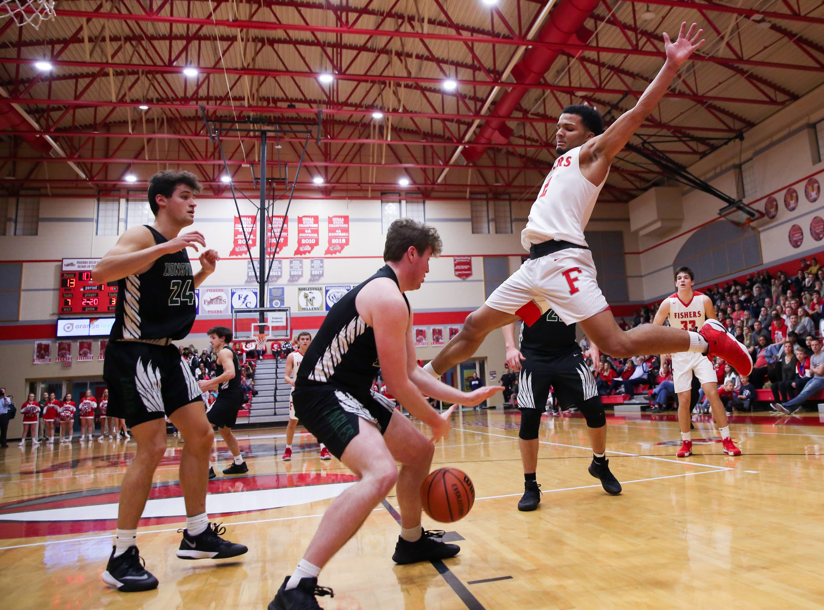 Fisher's Josiah Matthews (2) attempts to block a rebound from Zionsville Ben Alcock (20) during the first half of Zionsville vs. Fishers high school boys varsity basketball game held at Fishers High School, February 15, 2019.