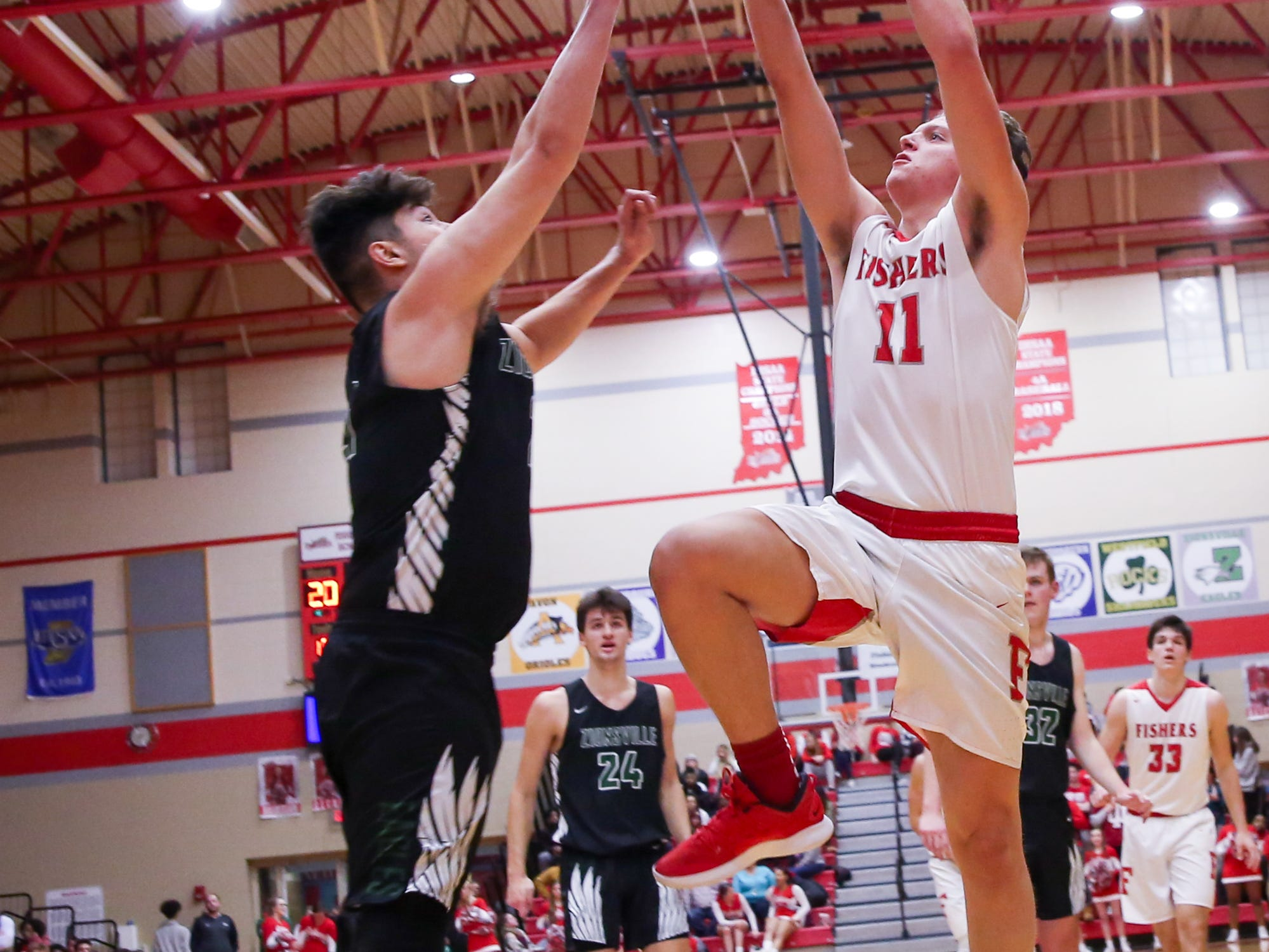 Fisher's Justin Long (11) drives to the basket during the first half of Zionsville vs. Fishers high school boys varsity basketball game held at Fishers High School, February 15, 2019.