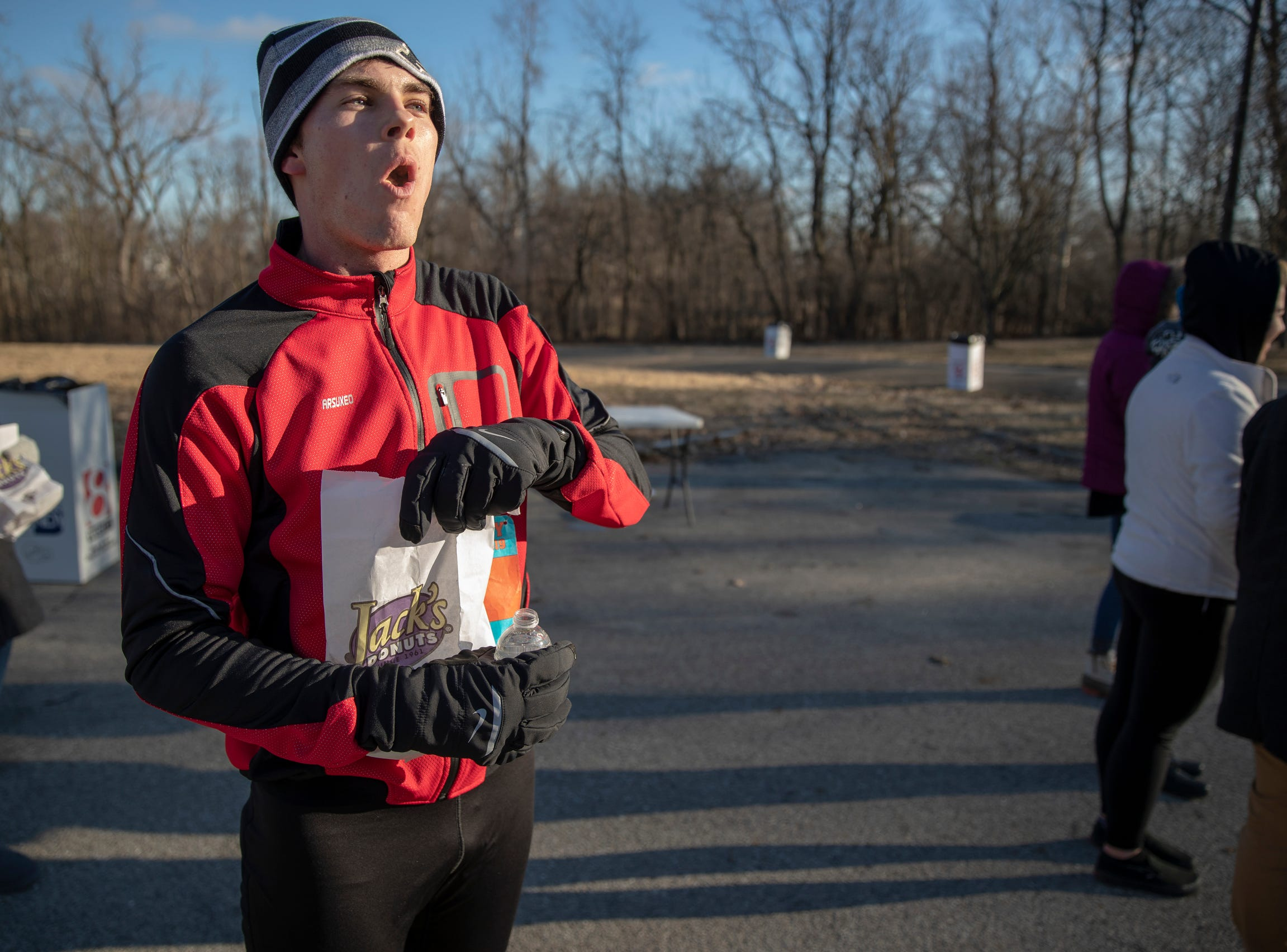Andrew Cartwright, who won the the Circle City Donut Dash 5k with a time of 19.52, gobbles down pastry during a five kilometer race that benefits Teachers' Treasures, Indianapolis, Saturday, Feb. 16, 2019. The race invites willing runners to eat a dozen doughnut holes at the halfway point in the event that helps provide school supplies for area school kids.