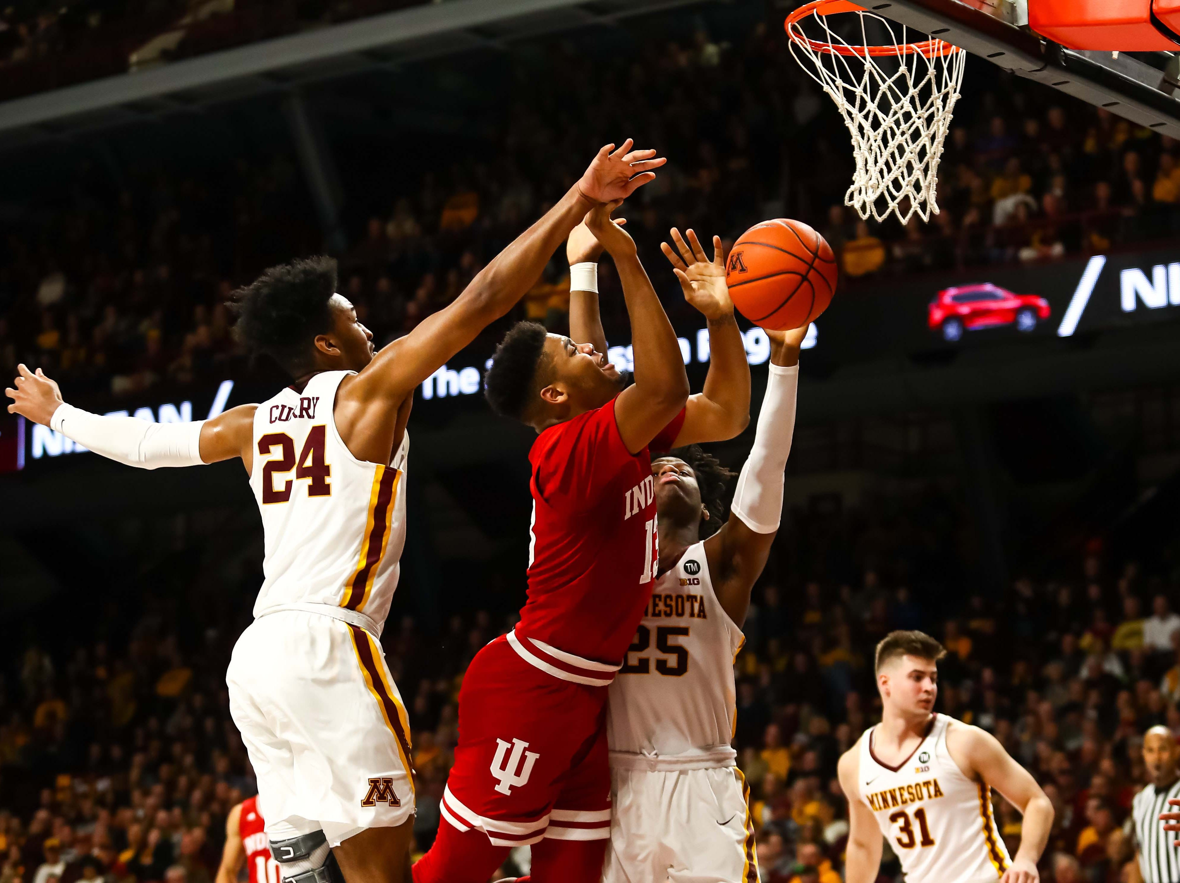 Feb 16, 2019; Minneapolis, MN, USA; Indiana Hoosiers forward Juwan Morgan (13) is fouled by Minnesota Golden Gophers center Daniel Oturu (25) in the second half at Williams Arena. The Minnesota Golden Gophers defeatd the Indiana Hoosiers 84-63. Mandatory Credit: David Berding-USA TODAY Sports