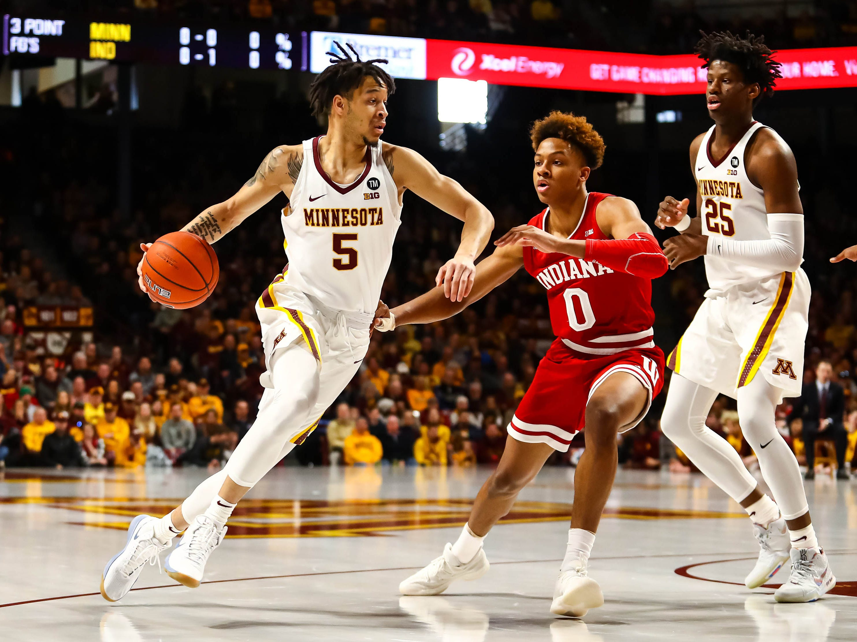 Minnesota Golden Gophers guard Amir Coffey (5) dribbles the ball while Indiana Hoosiers guard Romeo Langford (0) defends in the first half at Williams Arena.