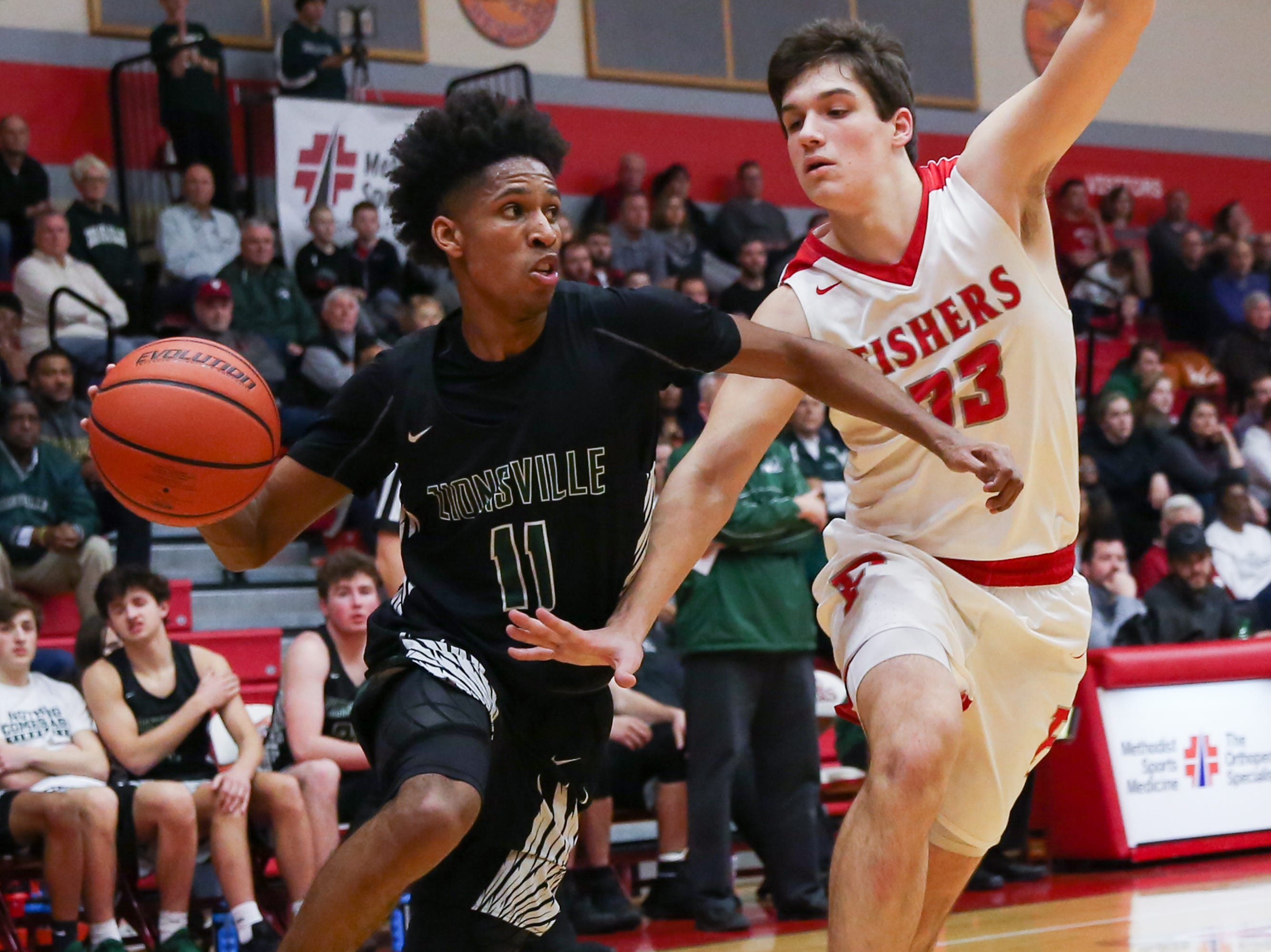 Zionsville Isaiah Thompson (11) makes a move around Fisher's Jeffrey Simmons (33) heading for the basket during the second half of Zionsville vs. Fishers high school boys varsity basketball game held at Fishers High School, February 15, 2019.