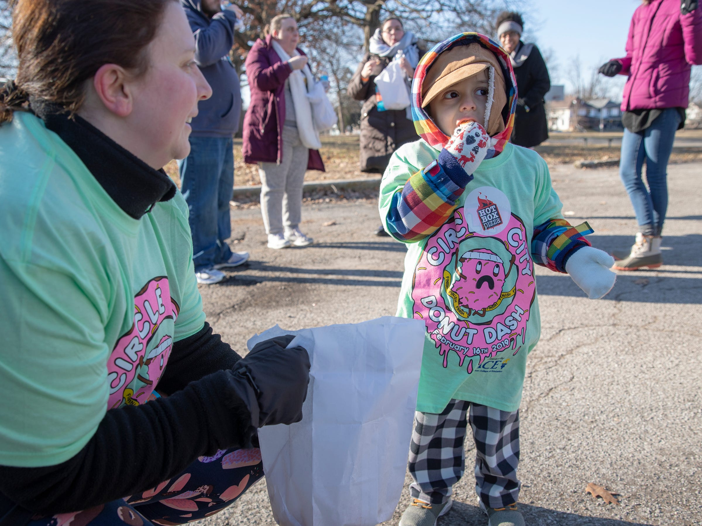 Vian Khatadia, 3, Brownsburg, has a doughnut hole with his mother Valerie Khatadia, during the Circle City Donut Dash 5k, a five kilometer race that benefits Teachers' Treasures, Indianapolis, Saturday, Feb. 16, 2019. The race invites willing runners to eat a dozen doughnut holes at the halfway point in the event that helps provide school supplies for area school kids.