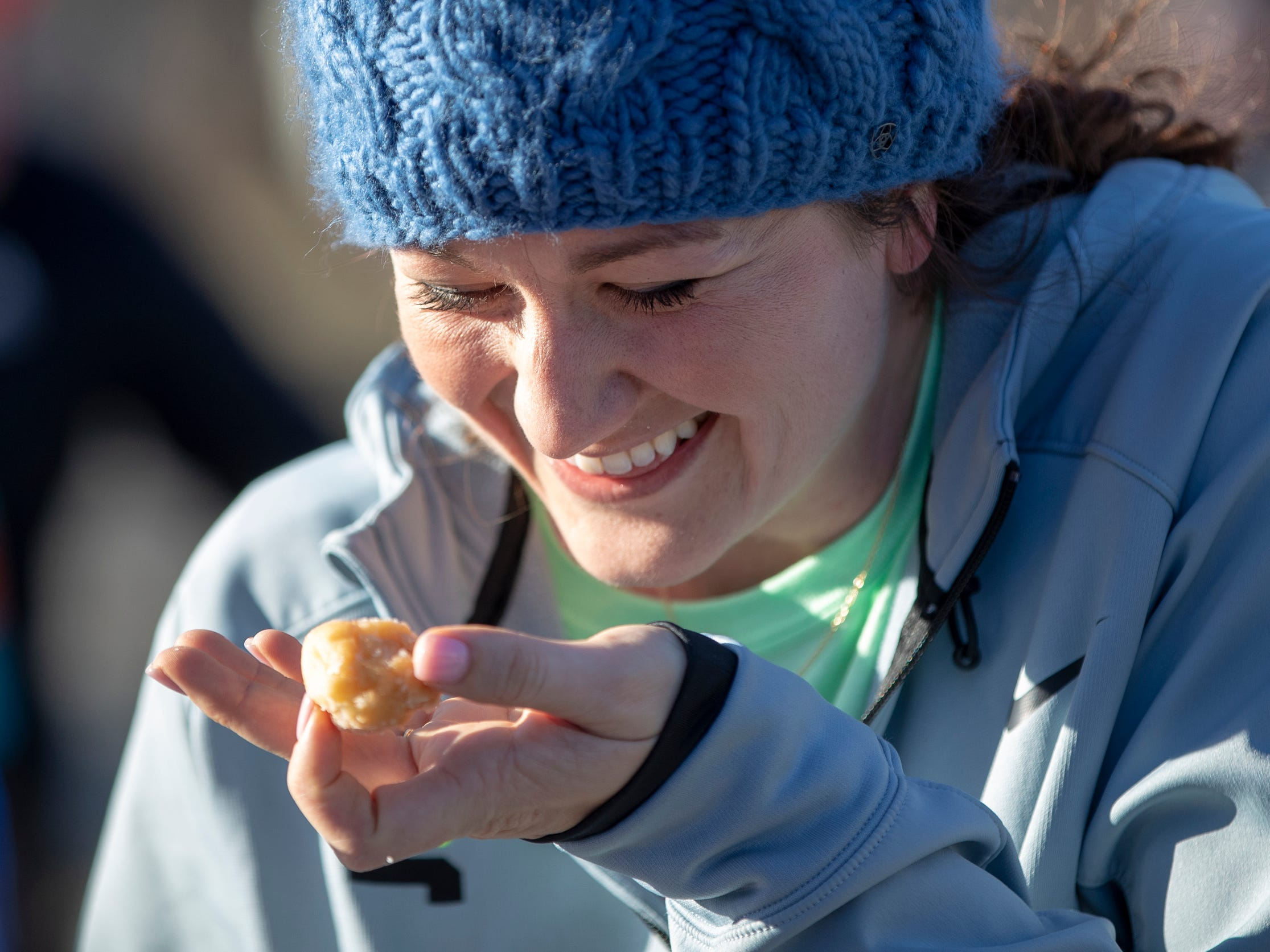 Blaire Barnhart laughs as she works on eating a doughnut hole during the Circle City Donut Dash 5k, a five kilometer race that benefits Teachers' Treasures, Indianapolis, Saturday, Feb. 16, 2019. The race invites willing runners to eat a dozen doughnut holes at the halfway point in the event that helps provide school supplies for area school kids.
