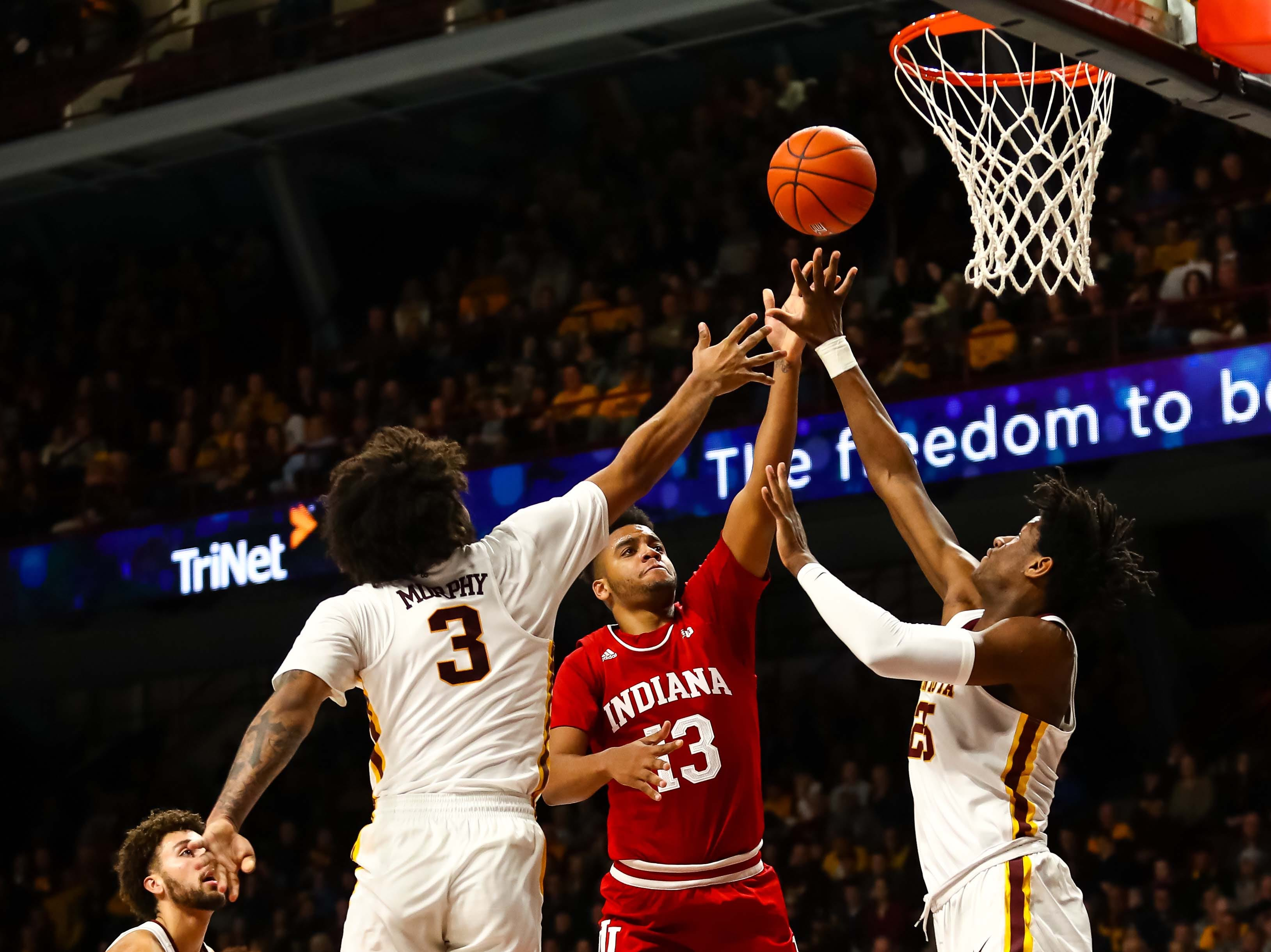Feb 16, 2019; Minneapolis, MN, USA; Indiana Hoosiers forward Juwan Morgan (13) goes up for a shot while Minnesota Golden Gophers forward Jordan Murphy (3) and center Daniel Oturu (25) defend in the second half at Williams Arena. The Minnesota Golden Gophers defeatd the Indiana Hoosiers 84-63. Mandatory Credit: David Berding-USA TODAY Sports