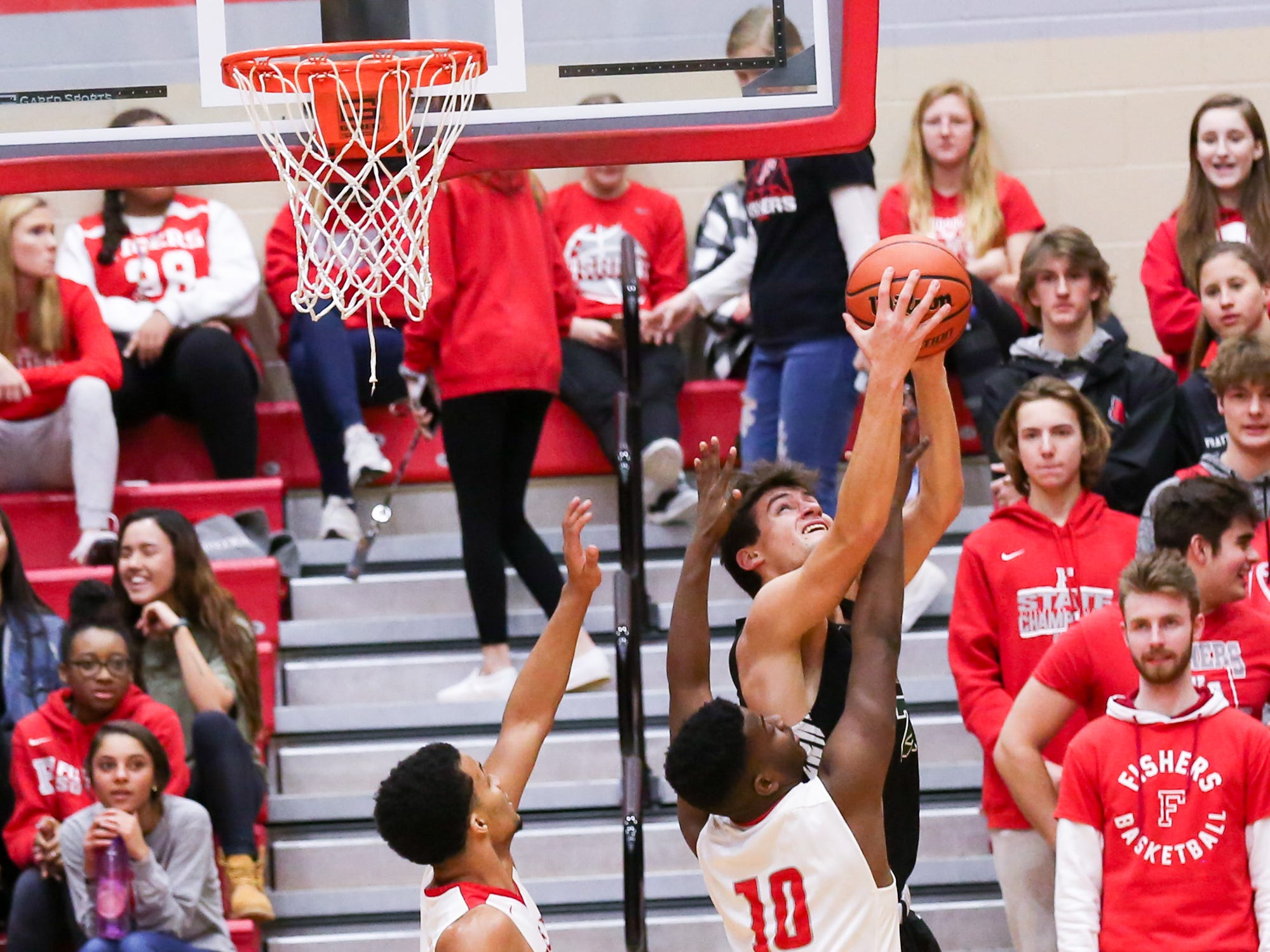 Zionsville Nathan Childress (24) and Fisher's Emmanuel Davis (10) fight for the rebound during the first half of Zionsville vs. Fishers high school boys varsity basketball game held at Fishers High School, February 15, 2019.