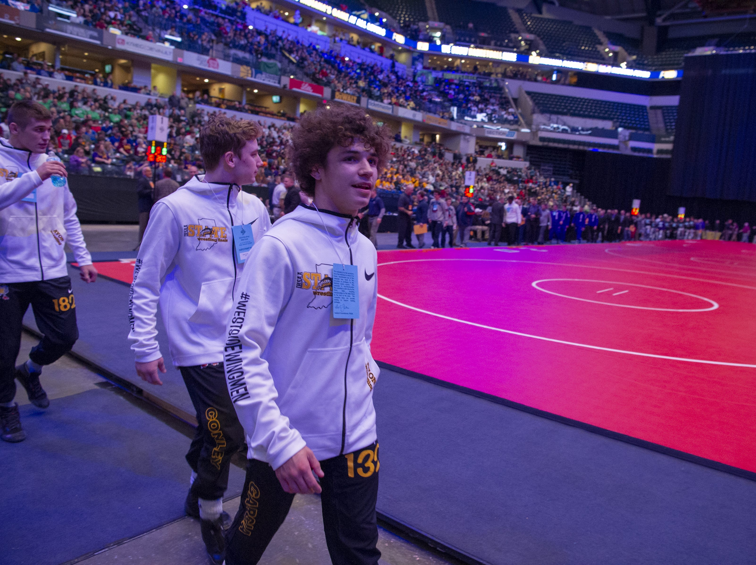 Avon High School wrestlers walk into the fieldhouse during team introductions before the first day of competition in the 81st Annual IHSAA Wrestling State Finals at Bankers Life Fieldhouse in Indianapolis, Friday, Feb. 15, 2019.