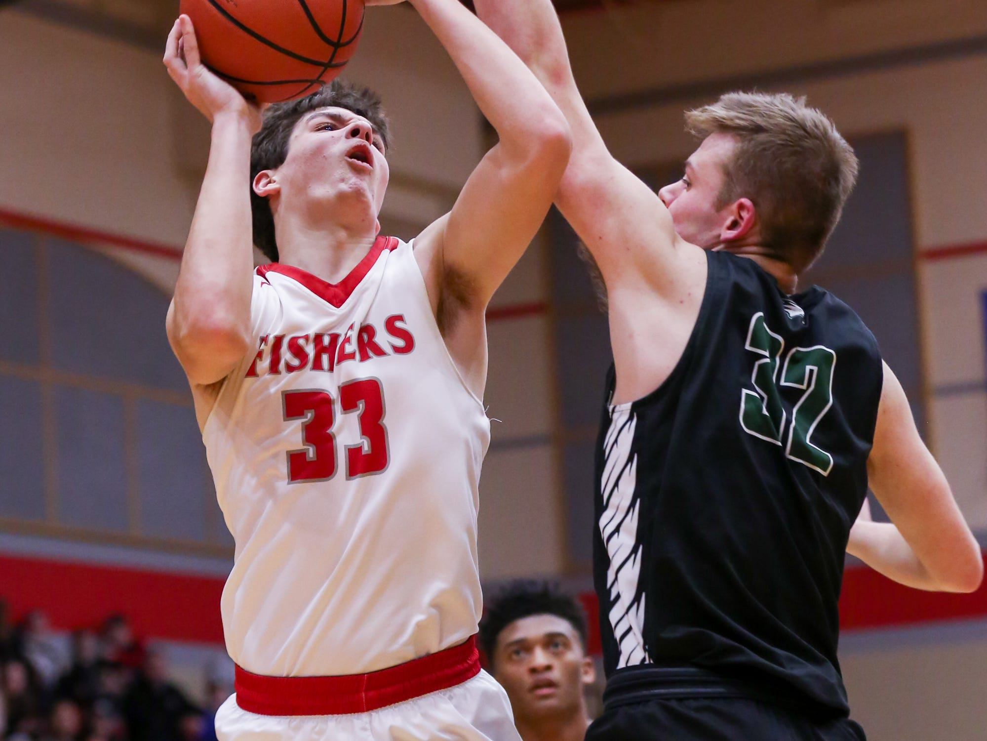 Fisher's Jeffrey Simmons (33) finds no opening around Zionsville Hogan Orbaugh (32) for a shot during the first half of Zionsville vs. Fishers high school boys varsity basketball game held at Fishers High School, February 15, 2019.