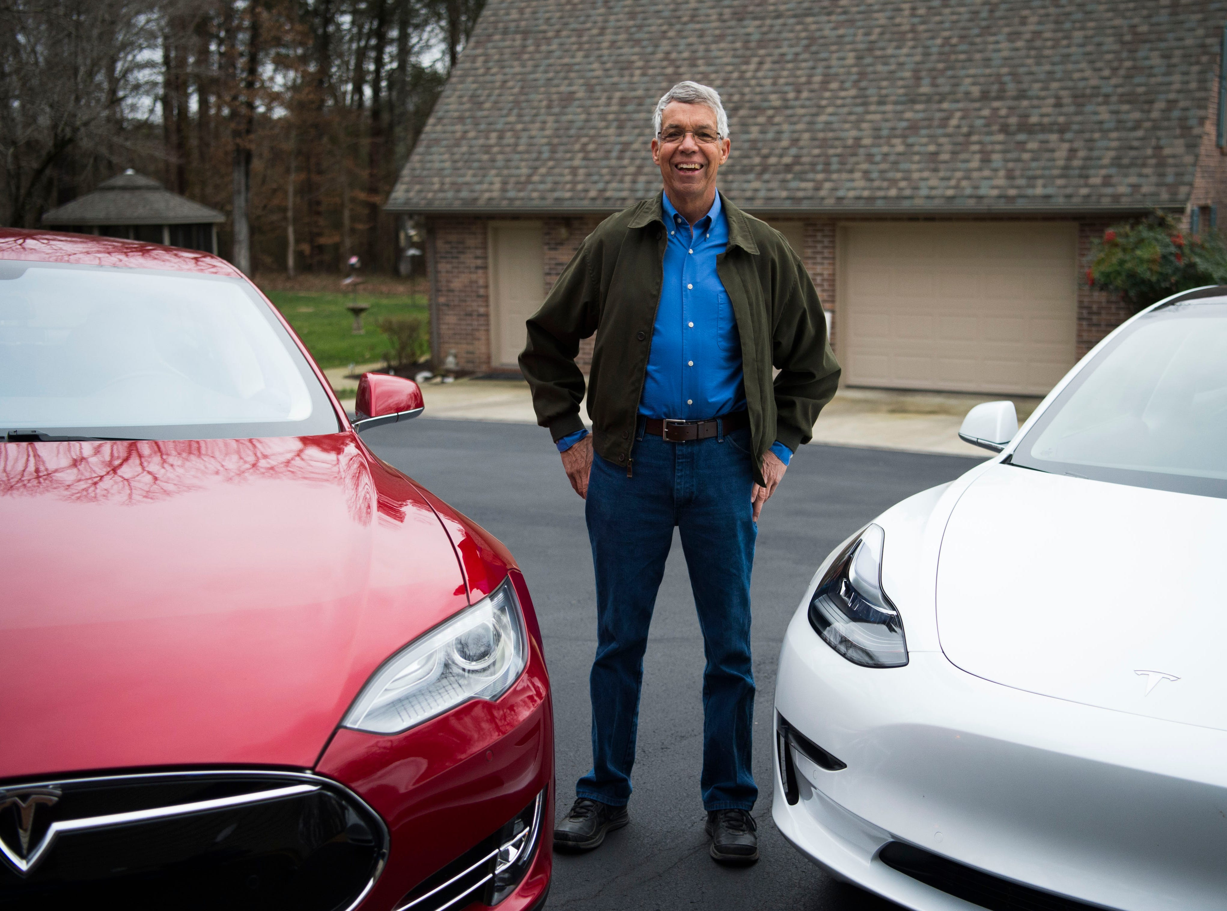 Mark Bishop stands next to his electric vehicles at his Clinton home Saturday, Feb. 16, 2019.