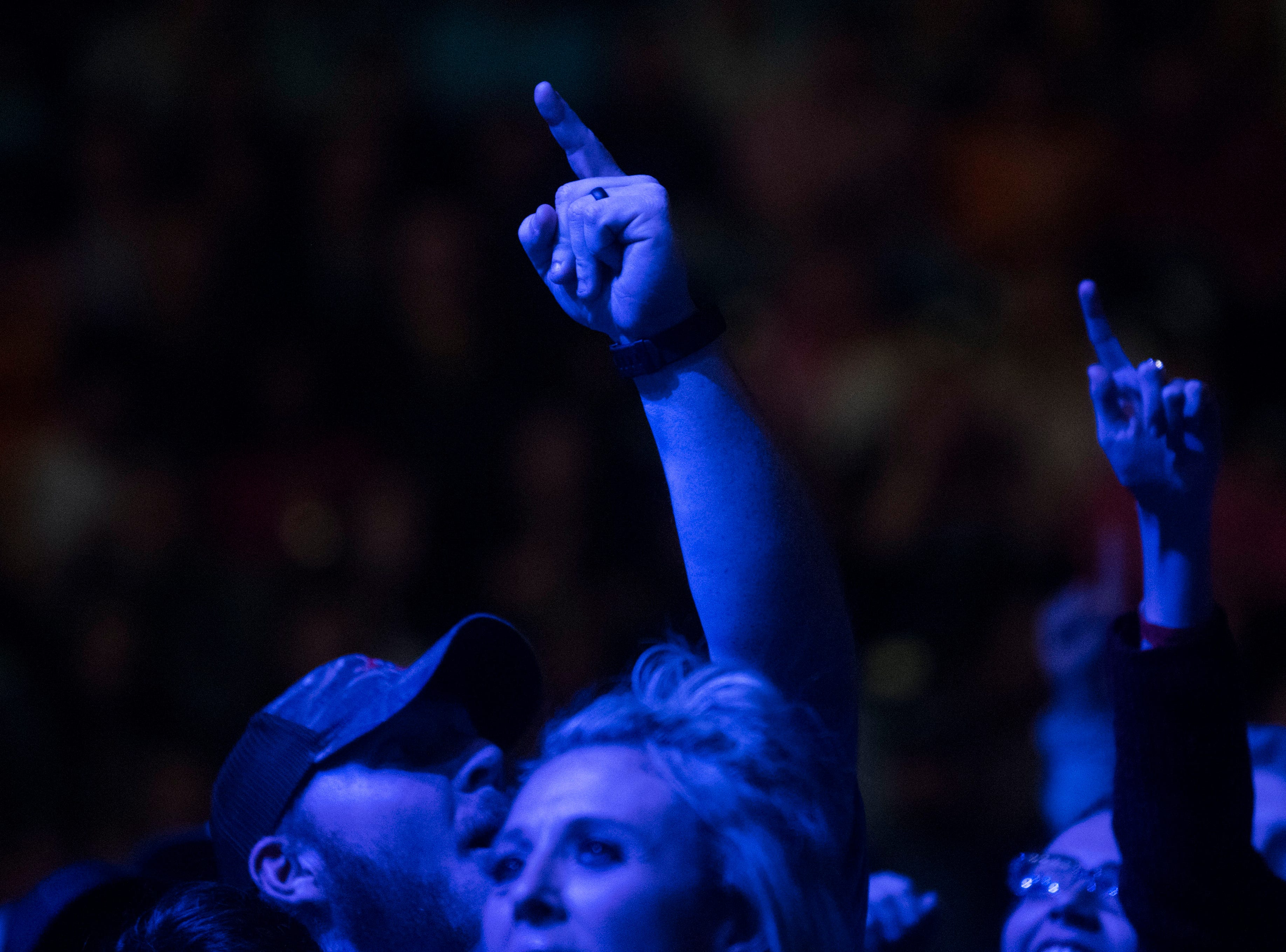 A fan raises their hand as Walker McGuire opens for Luke Combs in Thompson-Boling Arena in Knoxville Friday, Feb. 15, 2019.