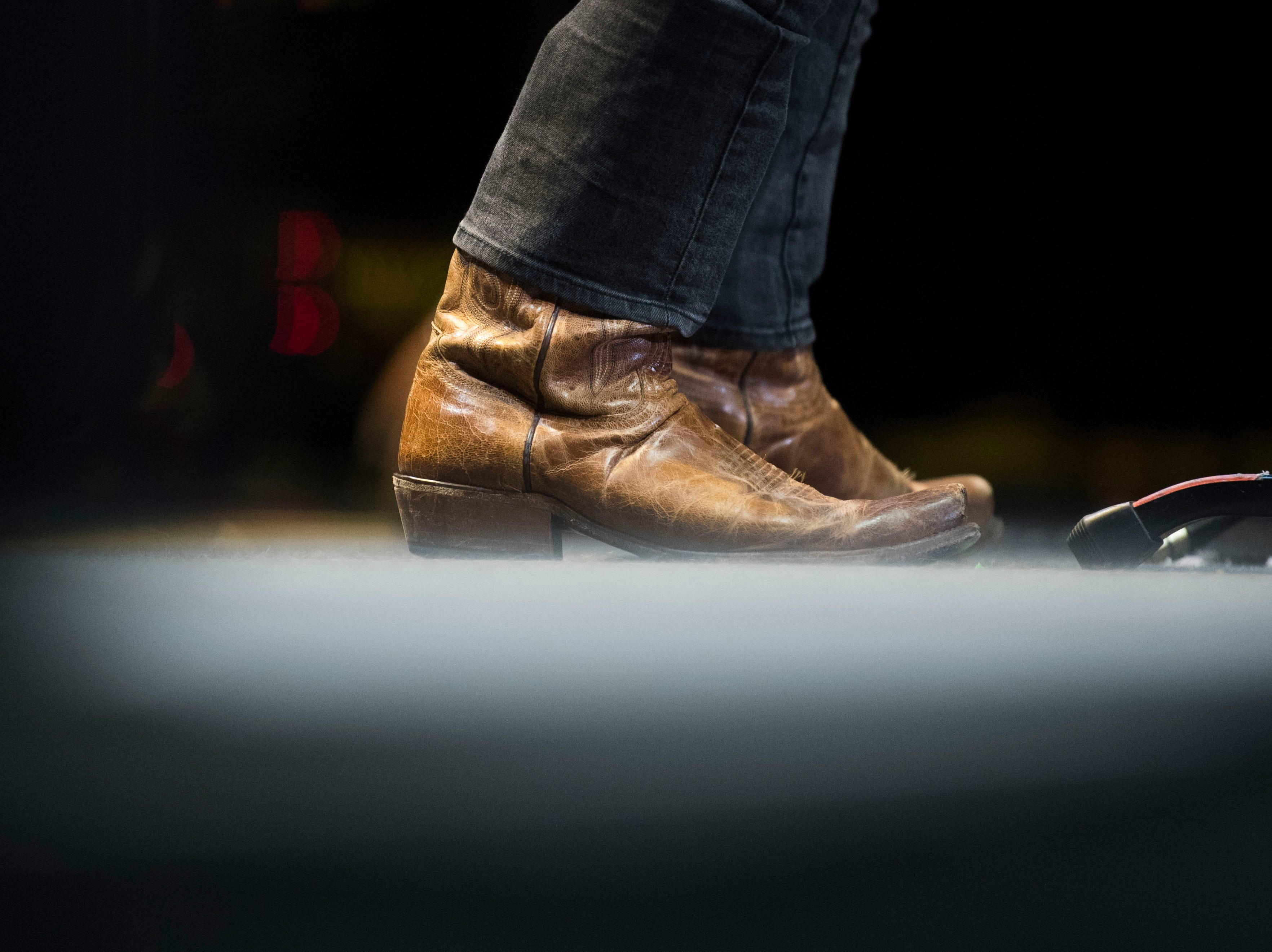 A musician's shoes are visible as Walker McGuire opens for Luke Combs in Thompson-Boling Arena in Knoxville Friday, Feb. 15, 2019.