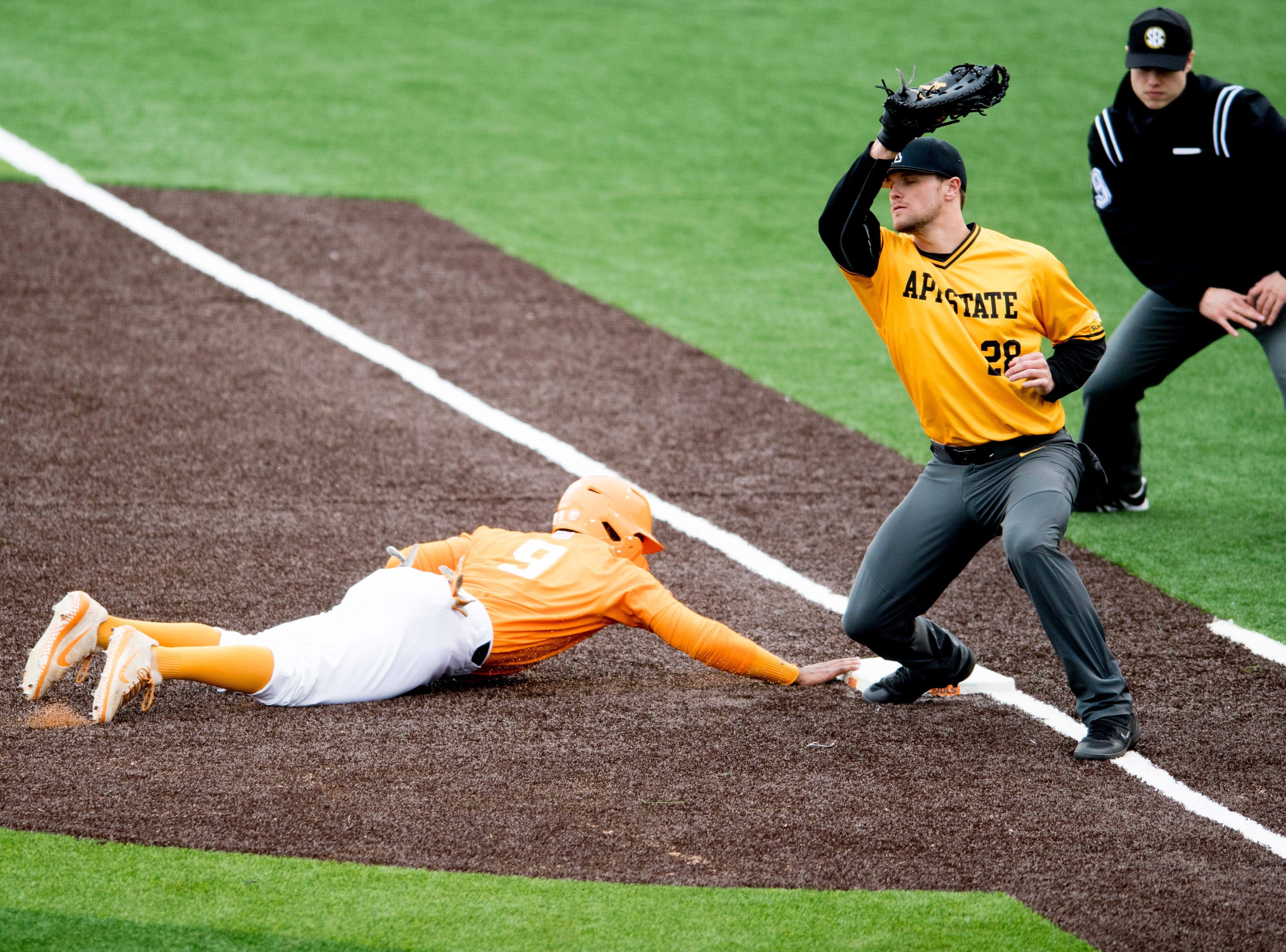 Tennessee outfielder Justin Ammons (9) slides safely into first as Appalachian State's Robbie Young (28) tries to out him during a Tennessee baseball home opener game against Appalachian State at Lindsey Nelson Stadium in Knoxville, Tennessee on Saturday, February 16, 2019.
