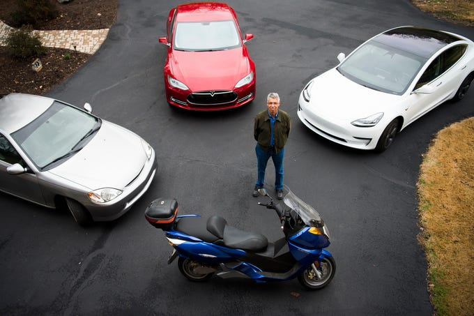 Mark Bishop stands next to his electric vehicles at his Clinton home Saturday, Feb. 16, 2019. From left is his 2000 Honda Insight which Bishop converted to an electric motor, A Tesla Model S, a Tesla Model 3, and a 2007 Vectrix motorcycle.