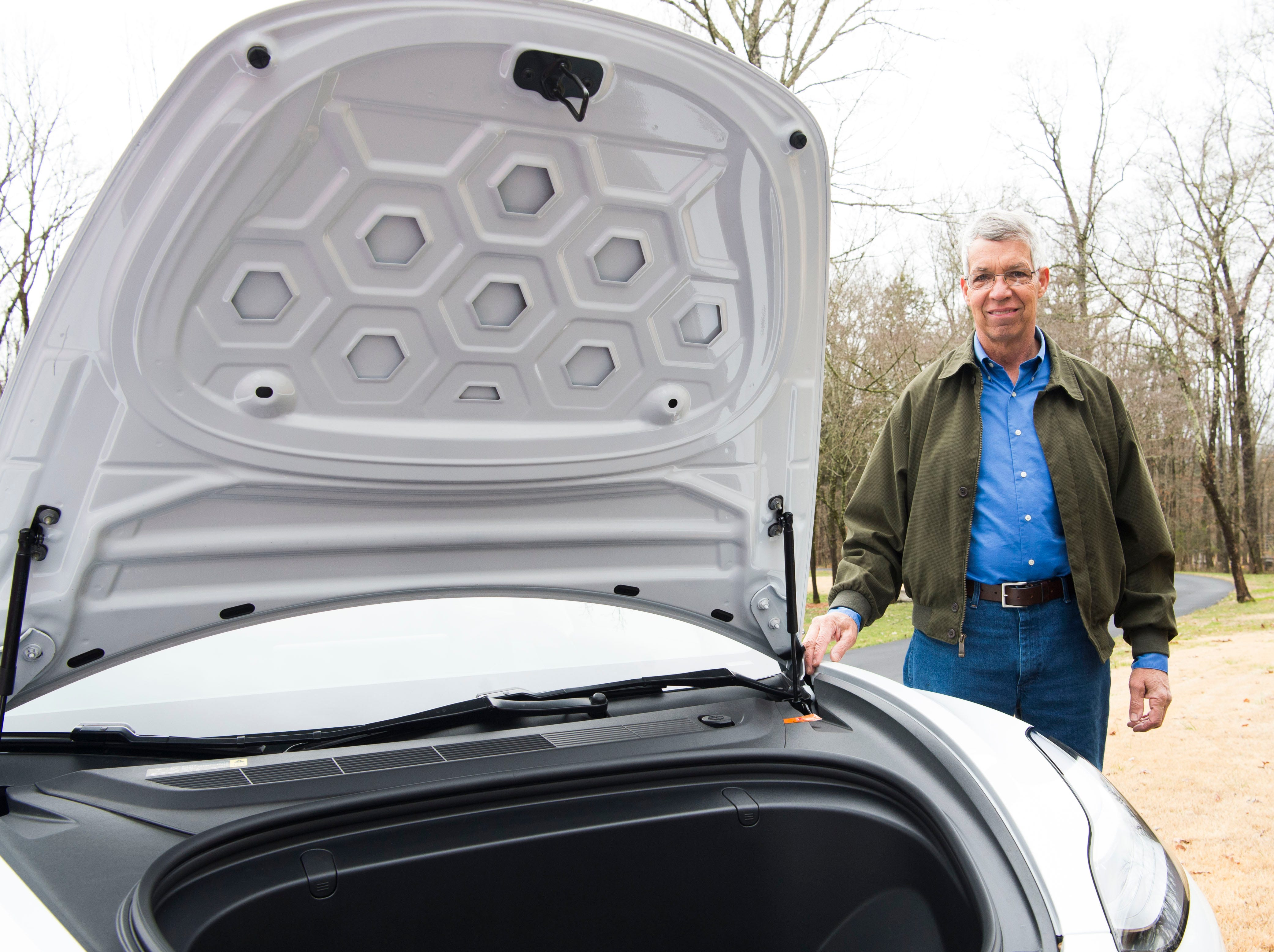 Mark Bishop stands next to his Tesla Model 3, which has has storage where a traditional motor would be, at his Clinton home Saturday, Feb. 16, 2019.
