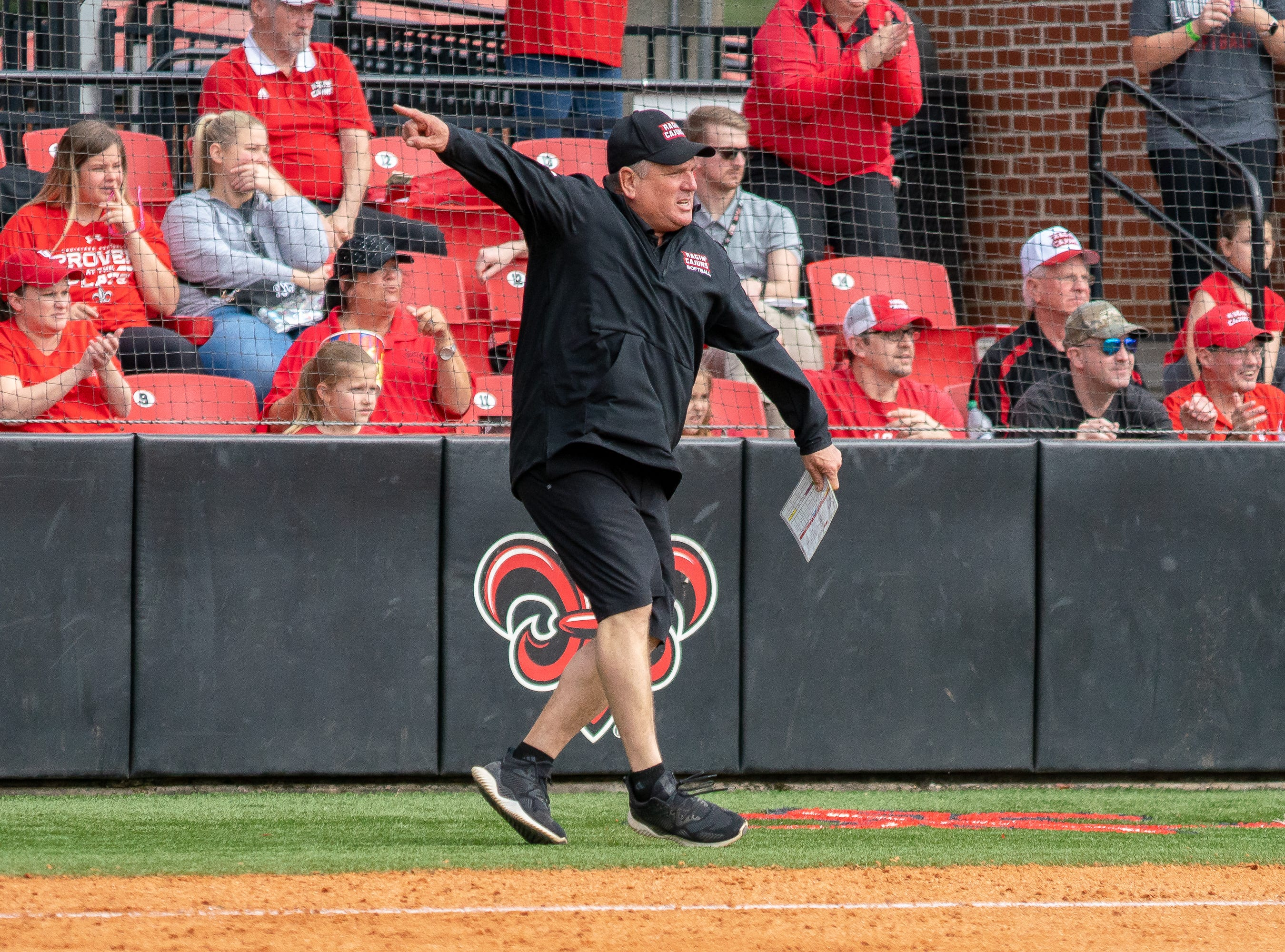 UL's head softball coach Gerry Glasco signals the runner to head for home plate as the Ragin' Cajuns take on Stephen F. Austin at Lamson Park on Saturday, Feb. 16, 2019.