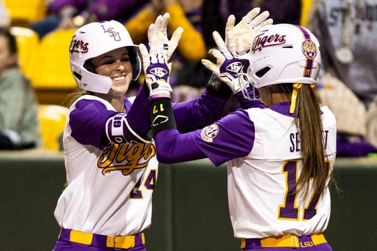 LSU softball players Amber Serrett (No. 17) and Claire Weinberger (No. 24) congratulate each other.