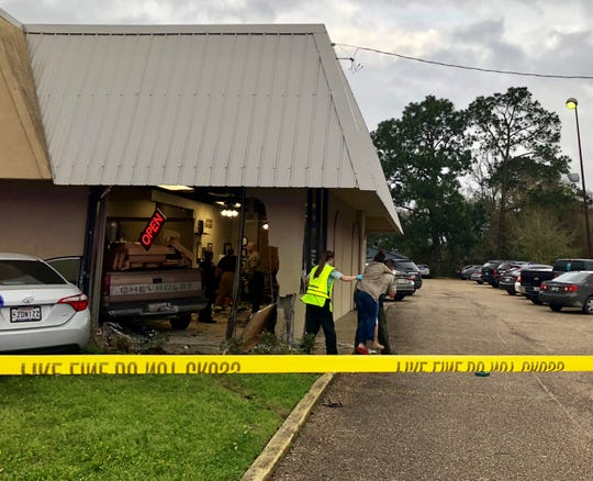 An injured woman is carried out of Princess Nails on Johnson Street. Injuries were reported Friday after a truck collided into the building while people were inside.