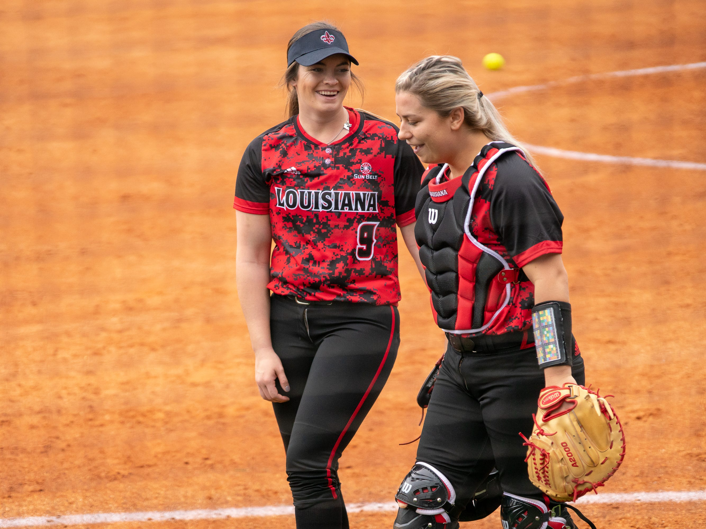 UL's Summer Ellyson (left) and Lexie Comeaux (right) laughing after the inning as the Ragin' Cajuns take on Stephen F. Austin at Lamson Park on Saturday, Feb. 16, 2019.