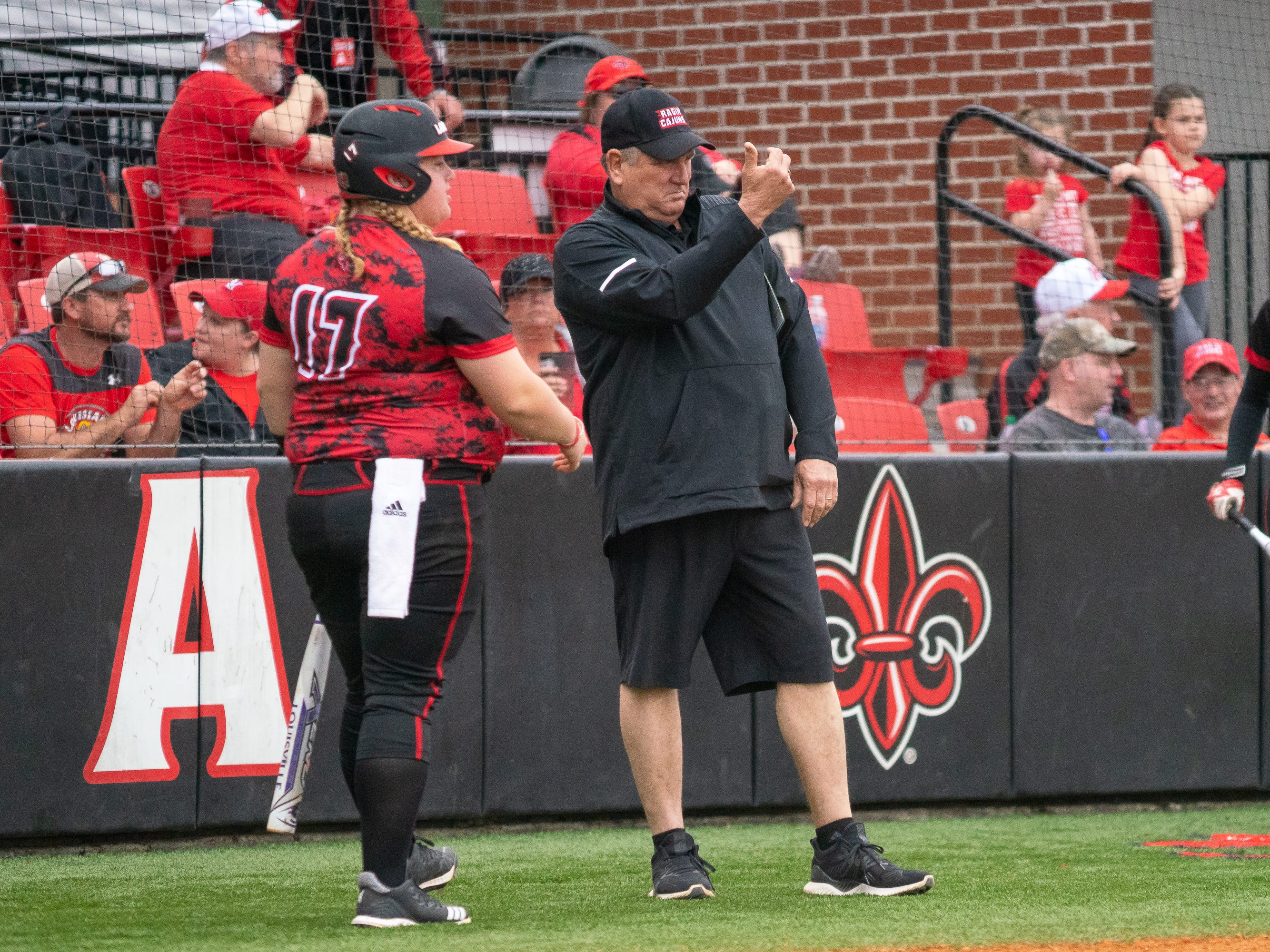 UL's head softball coach Gerry Glasco signals his players to come to the sidelines as the Ragin' Cajuns take on Stephen F. Austin at Lamson Park on Saturday, Feb. 16, 2019.