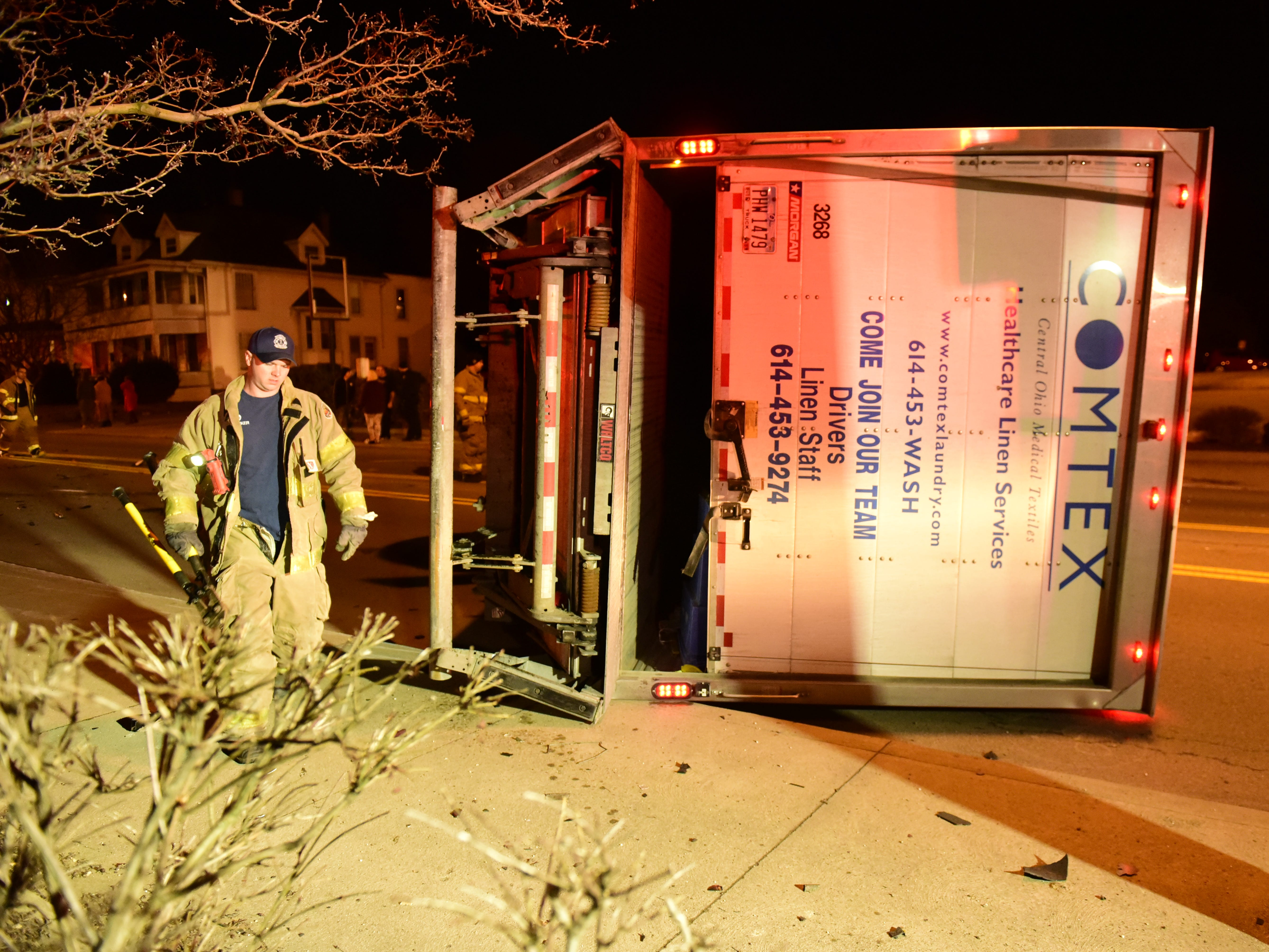 A firefighter walks around the rolled tractor-trailer Friday night.