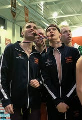 Galion's 400 freestyle relay members Alec Dicus and Ben Altstadt have some fun with their medals during Friday's Division II district swim meet at Bowling Green.