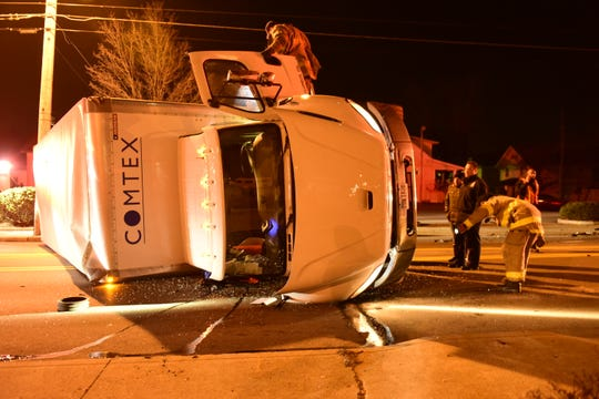 Firefighters look over the damage of a tractor-trailer that rolled about 9:30 p.m. Friday on South Main Street in Mansfield.
