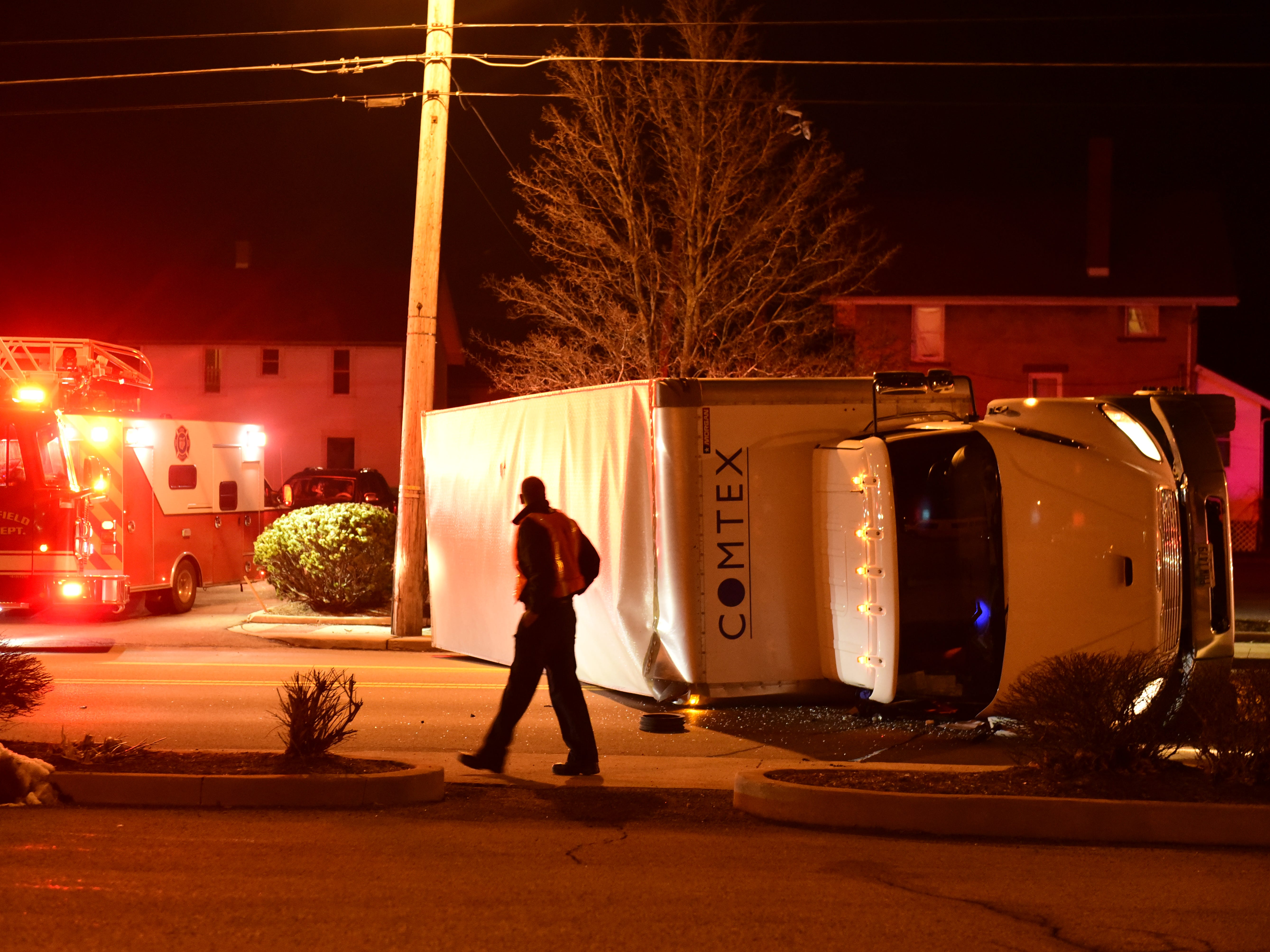 A police officer looks over the damage after a tractor-trailer rolled on South Main Street about 9:30 p.m. Friday.