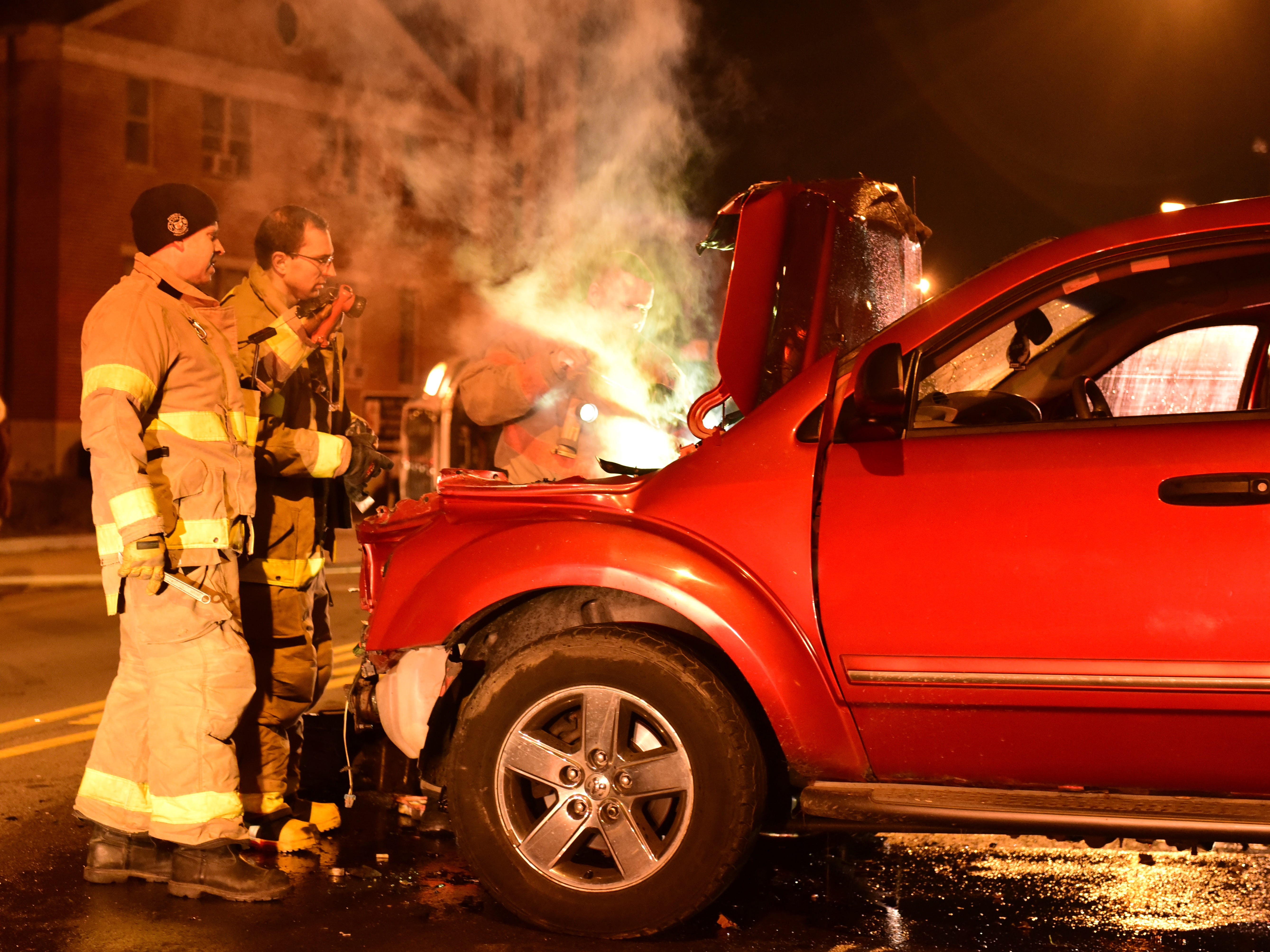 Firefighters take a look at the smoking radiator of the SUV involved in Friday's wreck.
