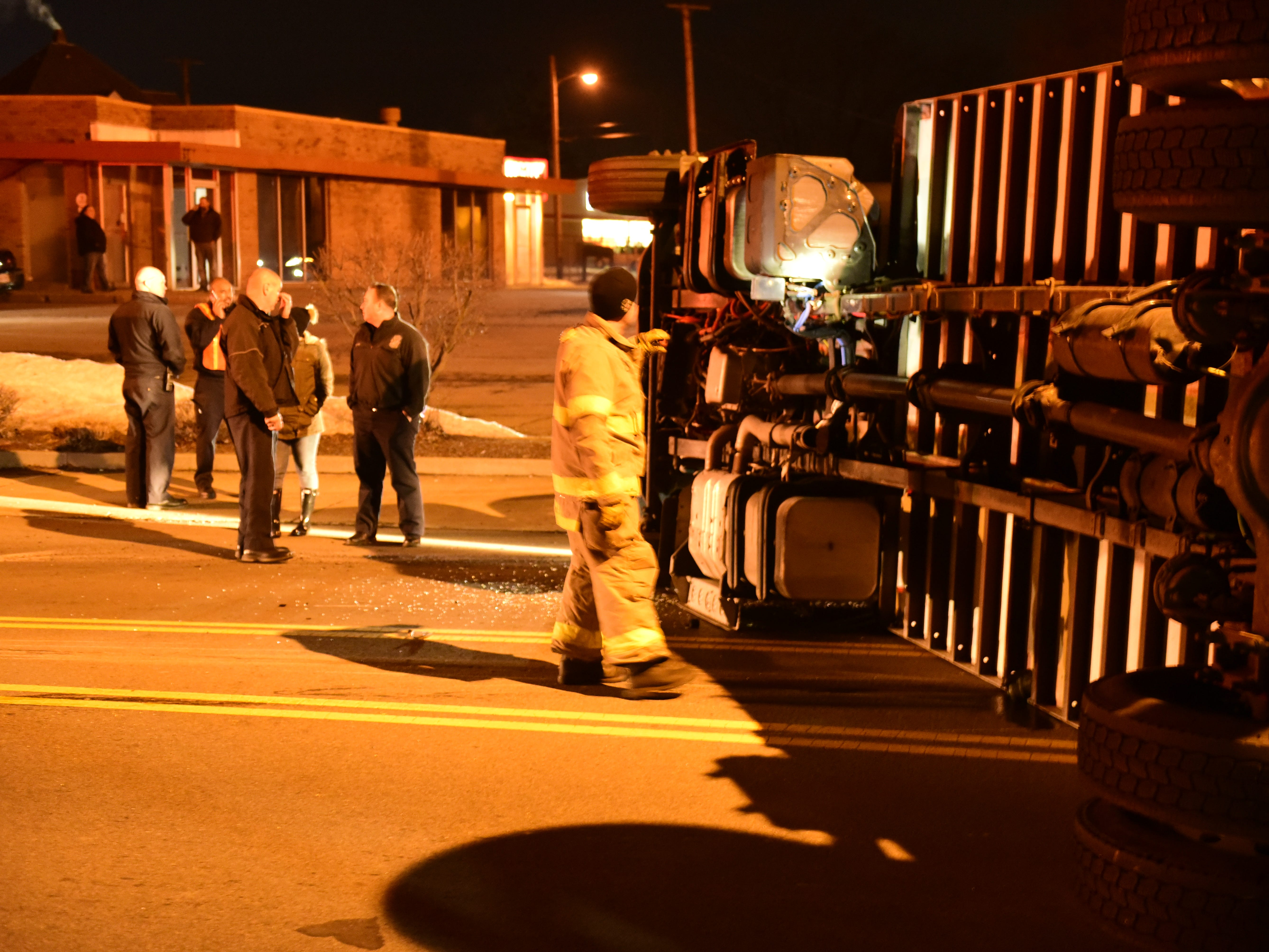 A firefighter looks a liquid dripping from a rolled tractor-trailer Friday night on South Main Street.