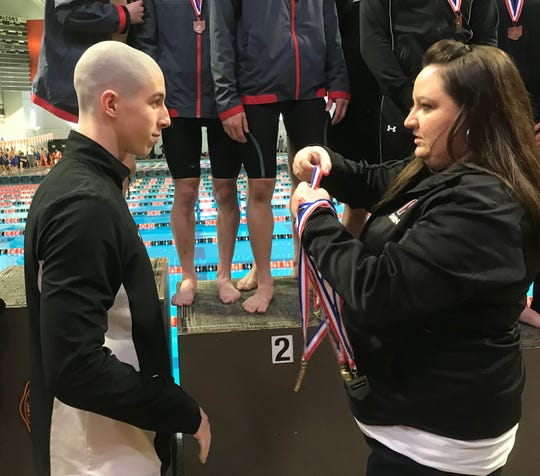 Lexington senior Wilson Cannon receives one of his four gold medals as a quadruple winner in Friday's Division II district swim meet at Bowling Green.