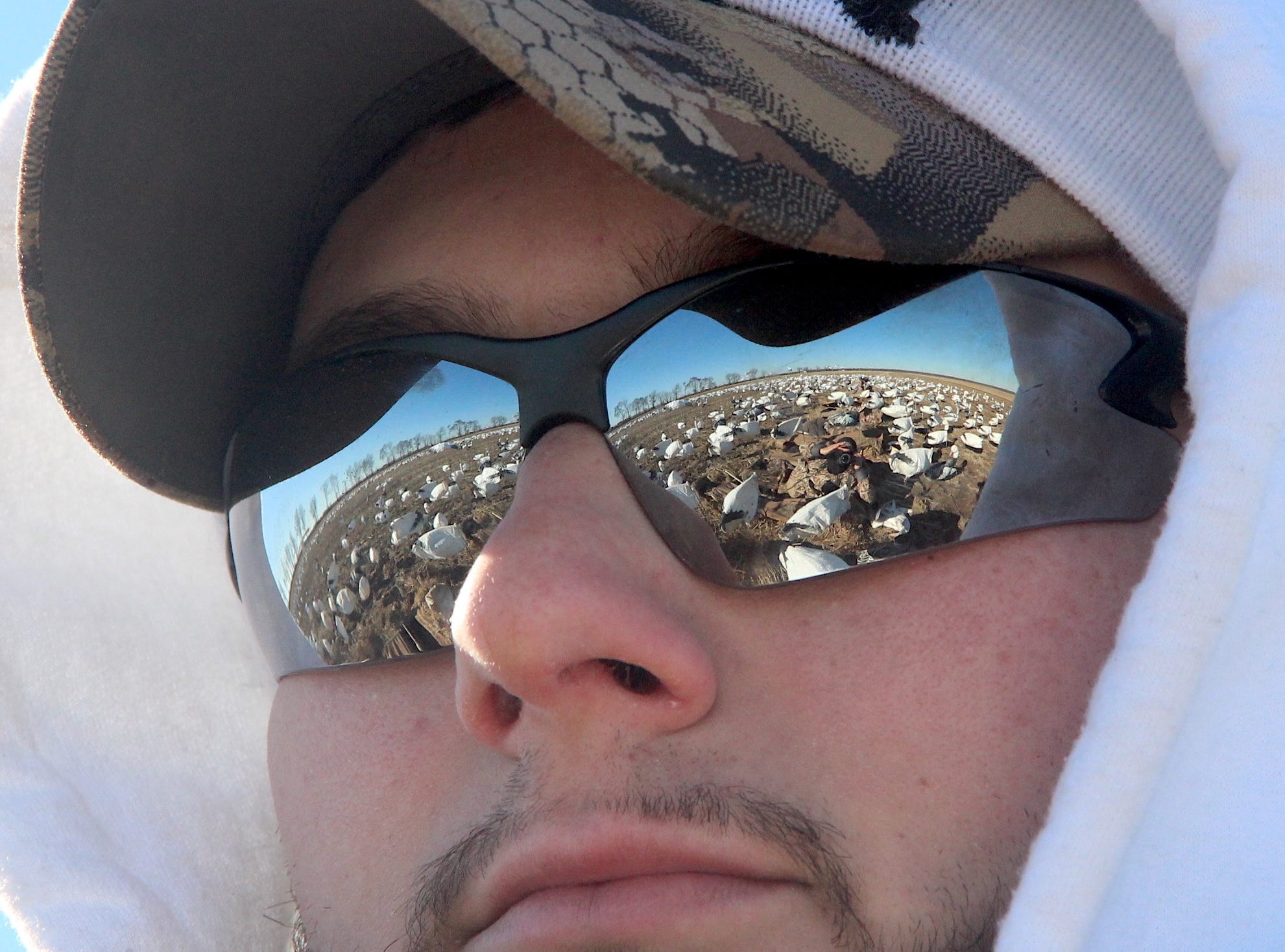 The spread of decoys and photographer are reflected in sunglasses worn by Conner Shepardson of Kaukauna, Wisconsin.