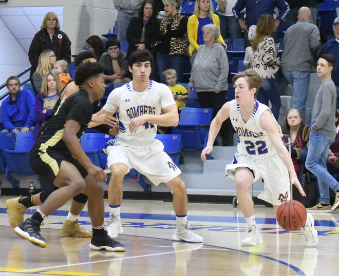 Mountain Home's Wyatt Gilbert (22) looks to drive to the basket while teammate Luke Kruse sets a screen against Nettleton on Friday night at The Hangar.